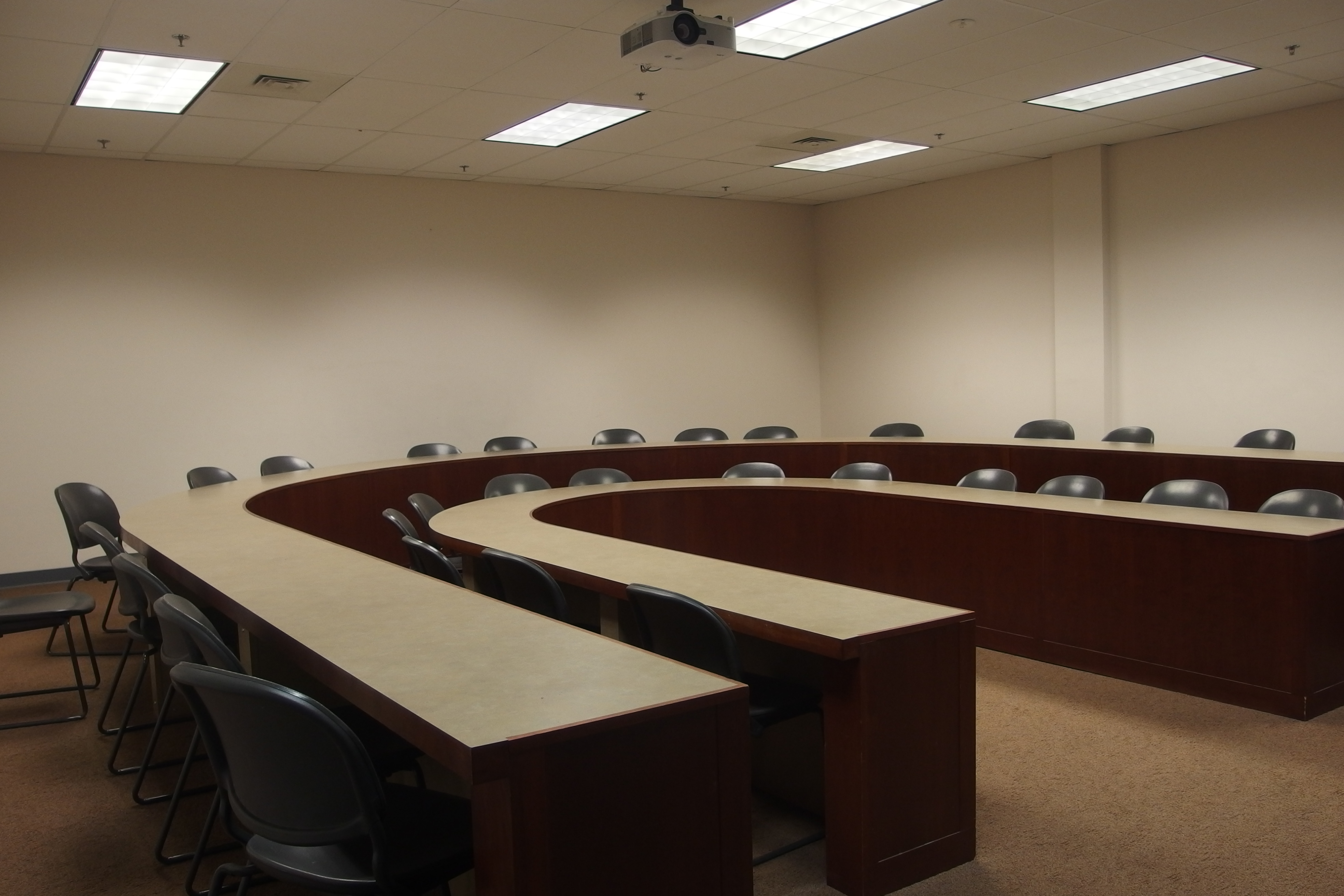 Photo of the classroom taken from the entrance of the space showing the U shape table configuration