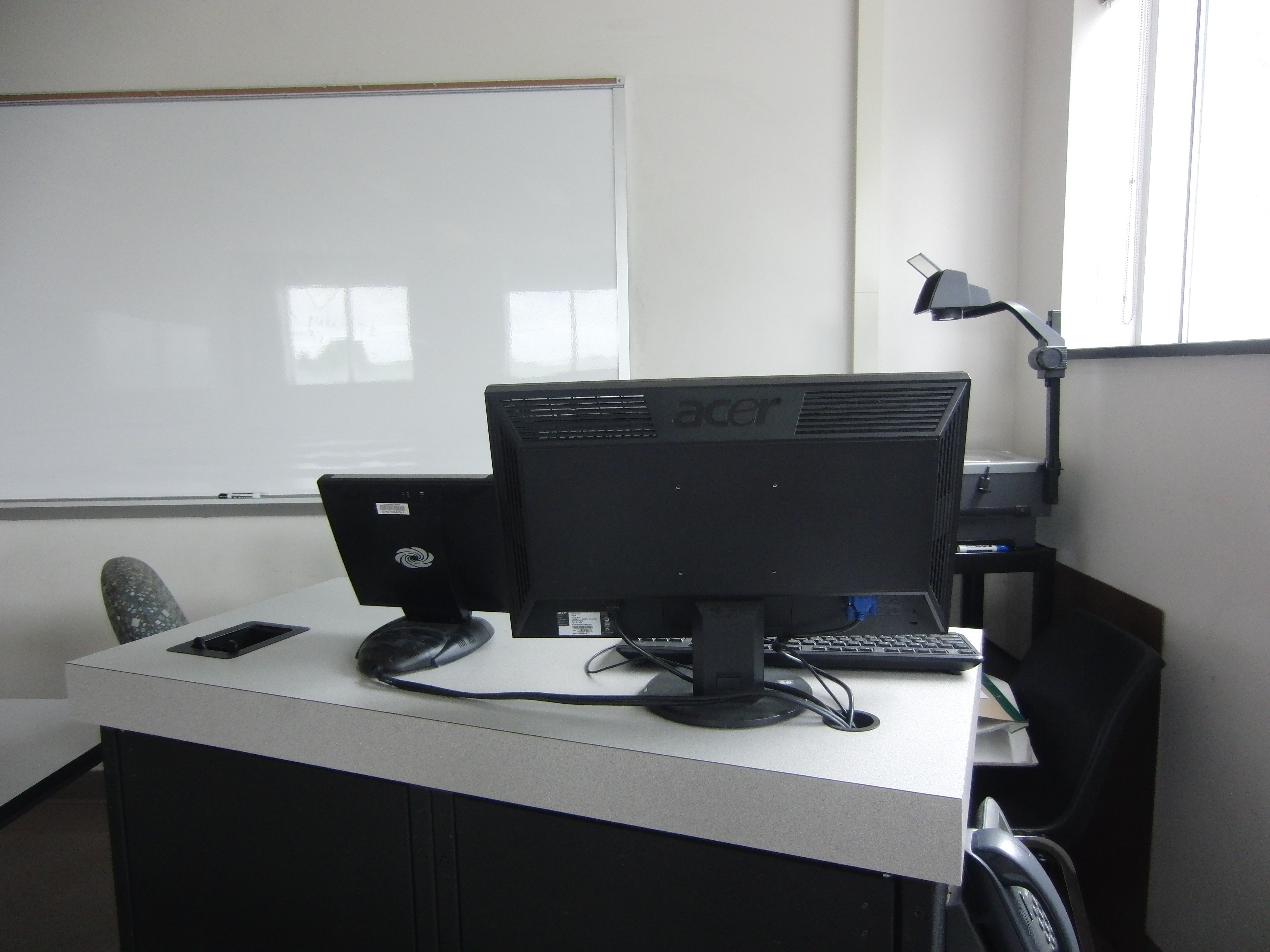 Photo of the back of the instructor station showing the computer monitor, the crestron control touch panel, and a phone
