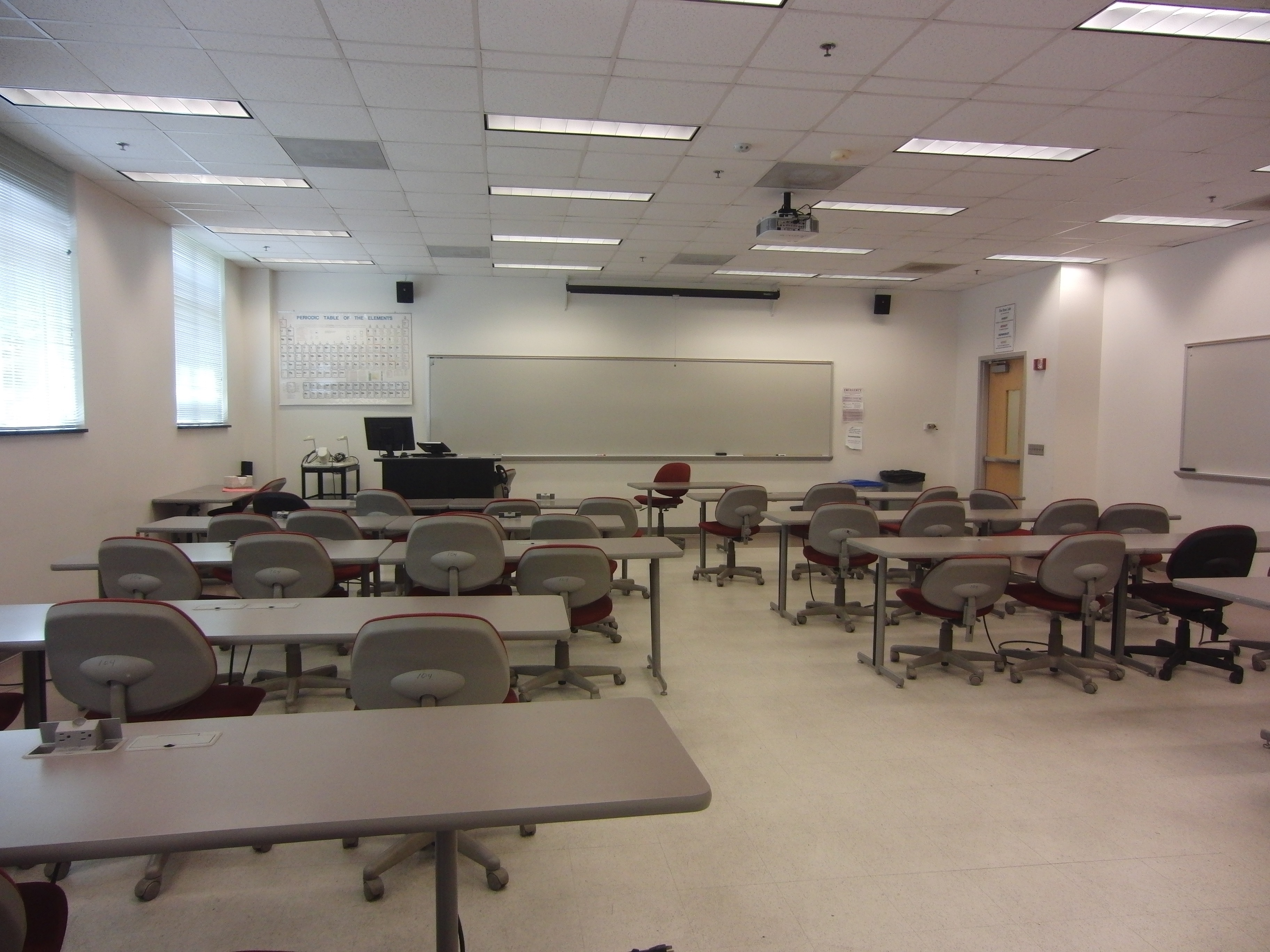Photo of the classroom space taken from the back of the room showing the stationary furniture, the mobile chairs, the instructor station, the exit door, and a white board