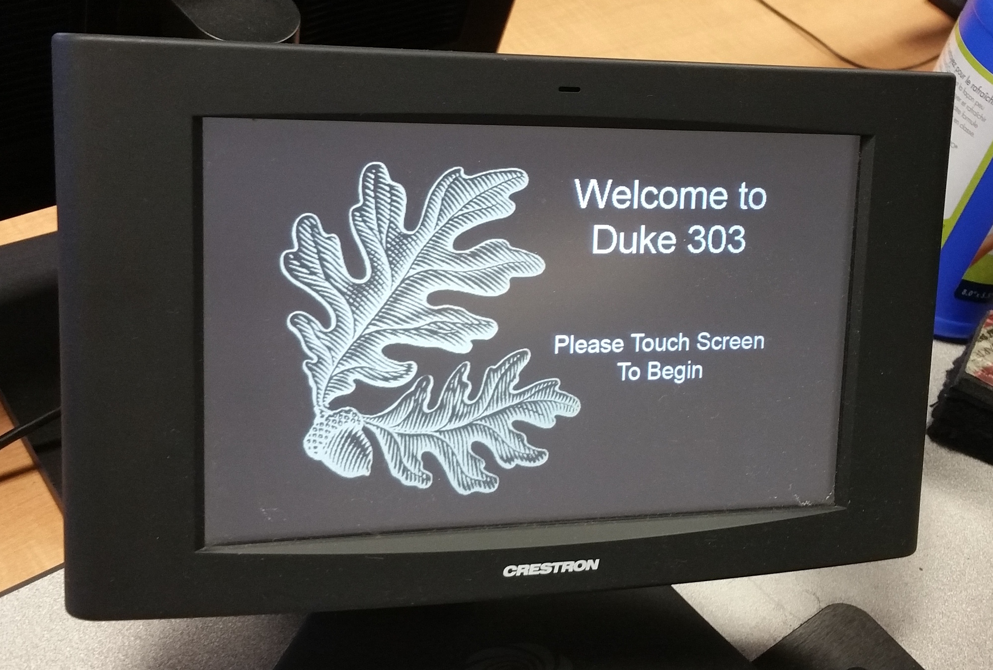 Photo of crestron control touch panel initial screen with instructions to touch screen to begin