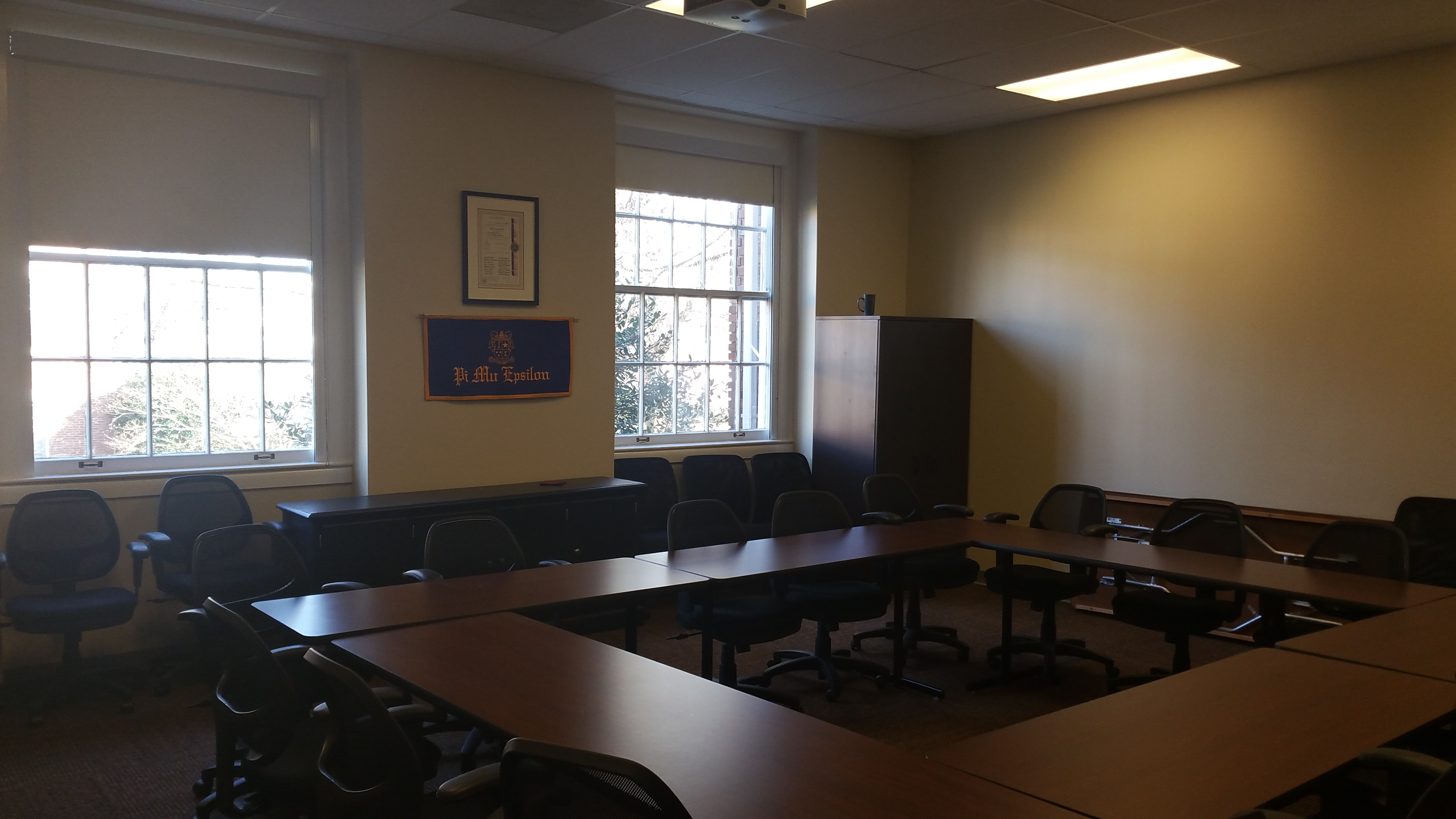 Photo of classroom taken from front of the room showing student tables and windows