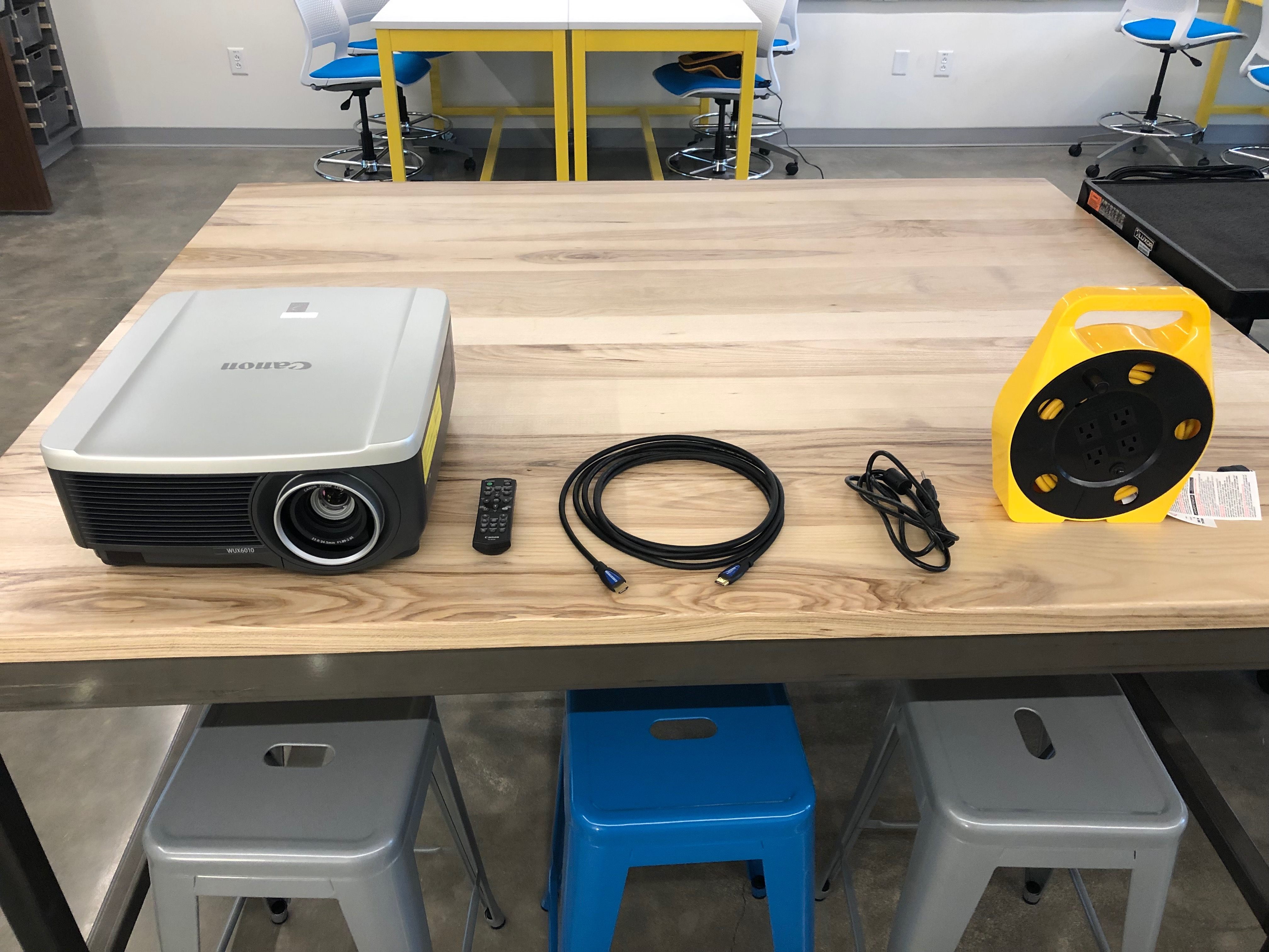 A photo of the items that are stored in the storage cabinet. (A Canon projector, Canon remote control, 12ft HDMI cable, projector power cable, power extension reel)