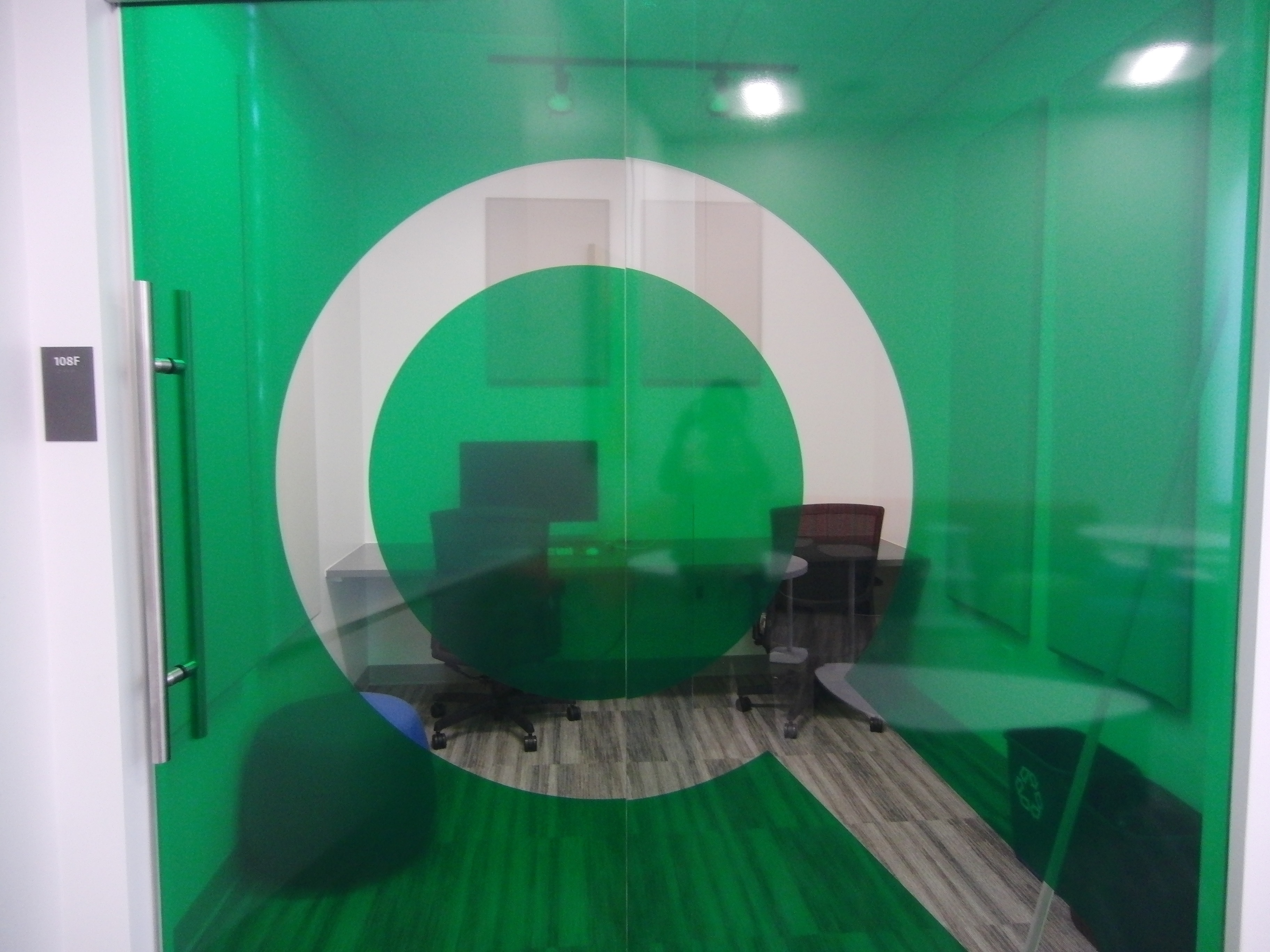Photo of the space taken from outside of the green glass door