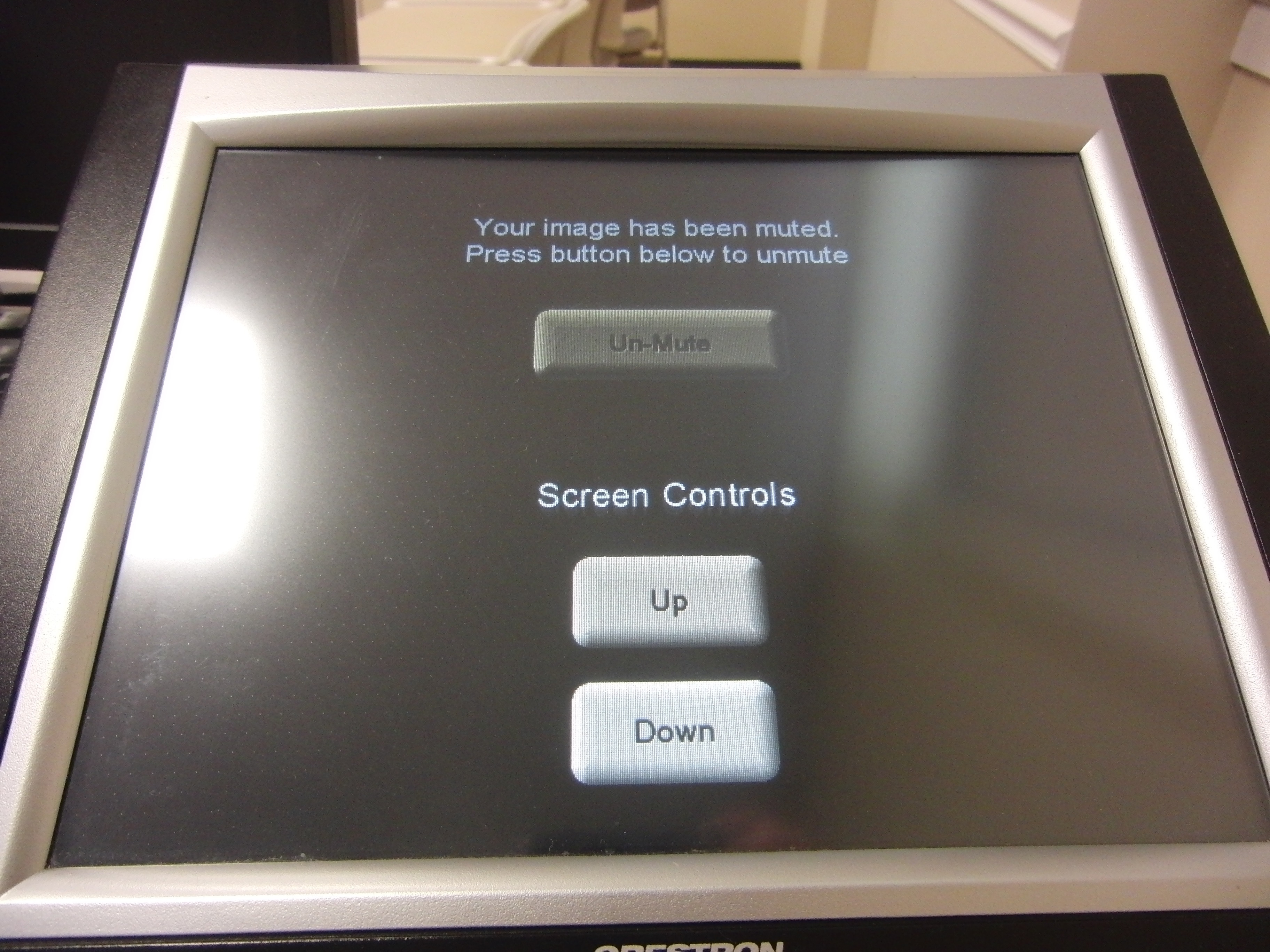 Photo of crestron control touch panel with option to un-mute the screen or move the screen up or down