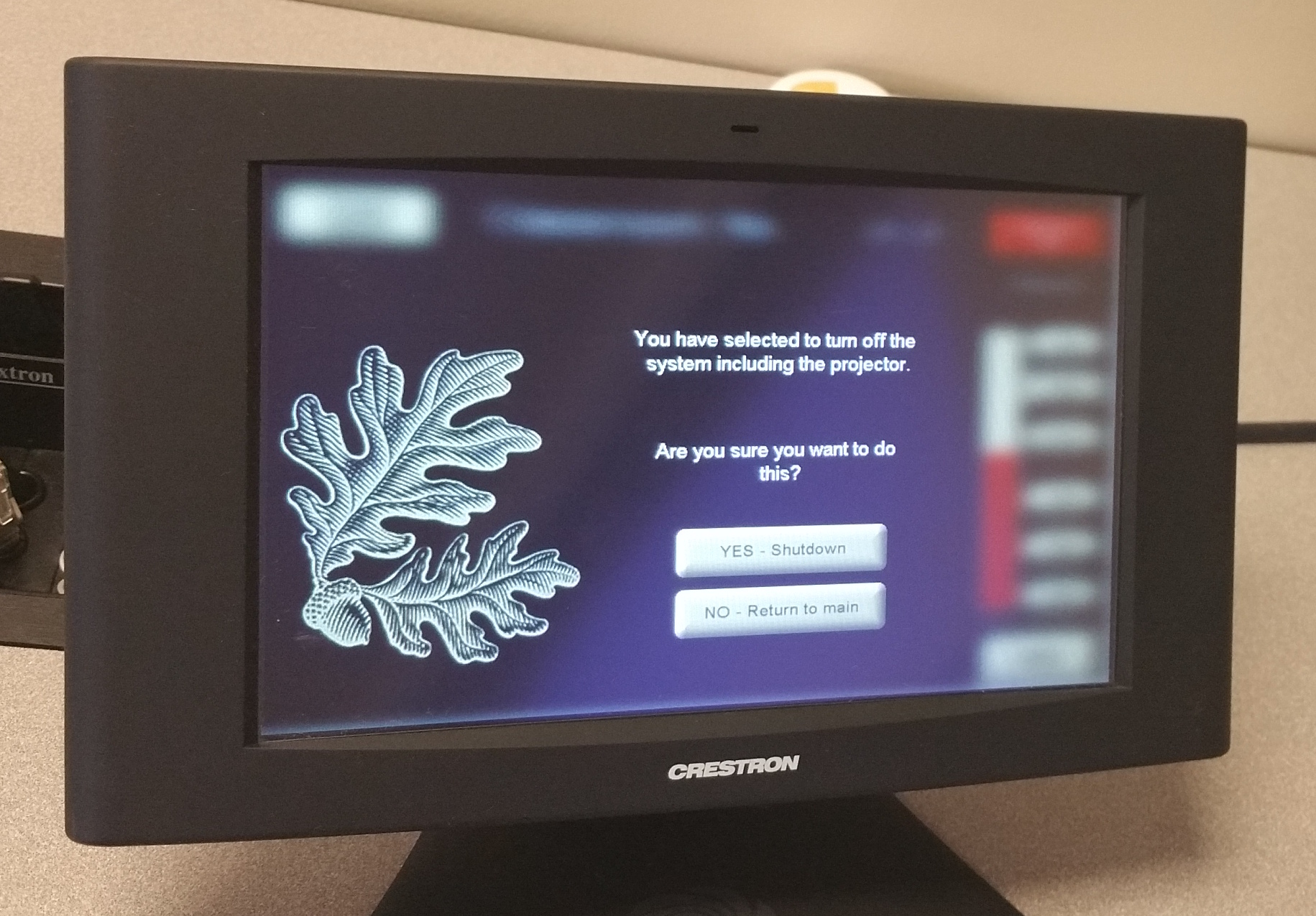 Photo of crestron control touch panel with shutdown screen active