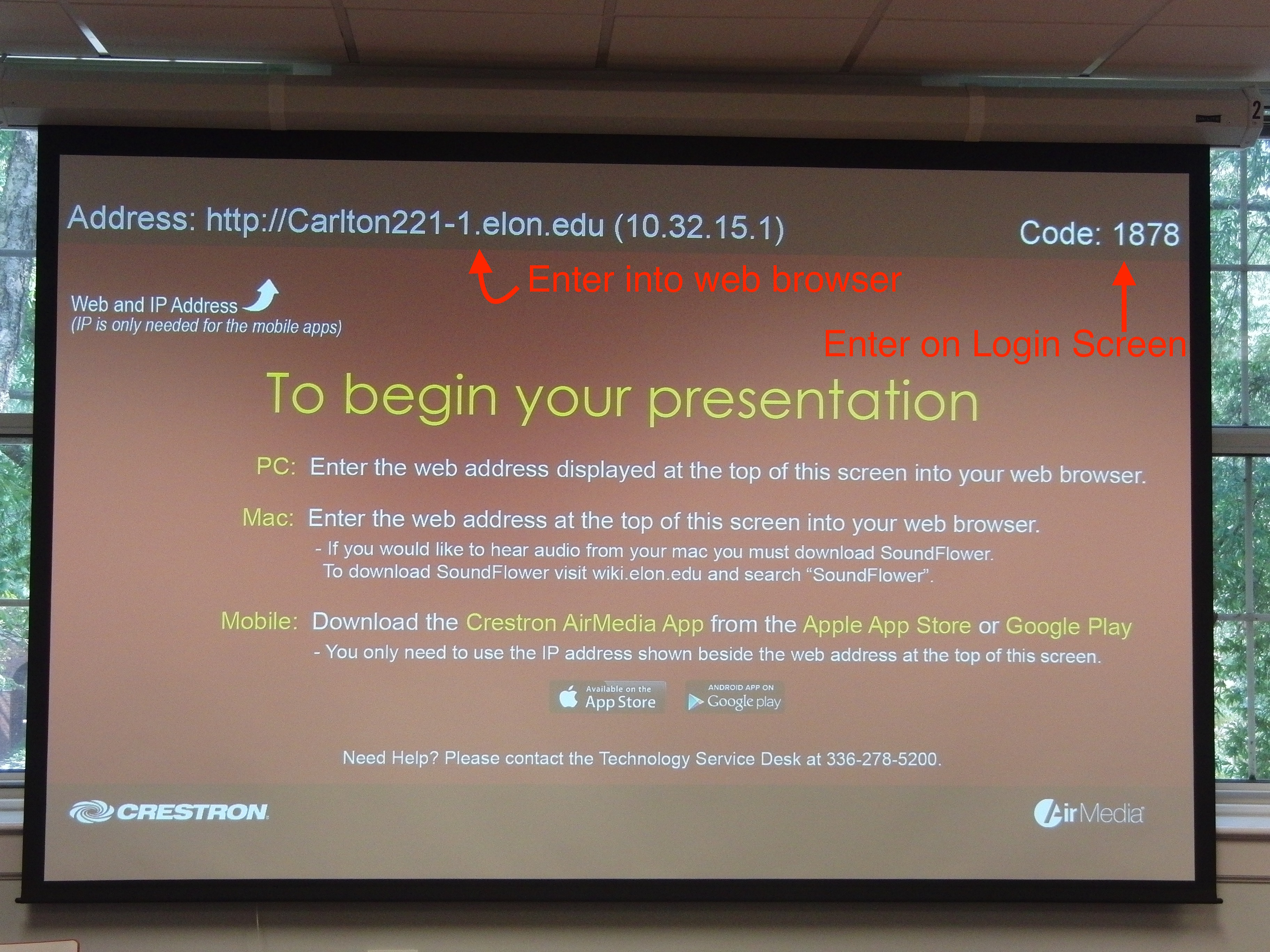 Photo of projection screen highlighting AirMedia information including web address and code
