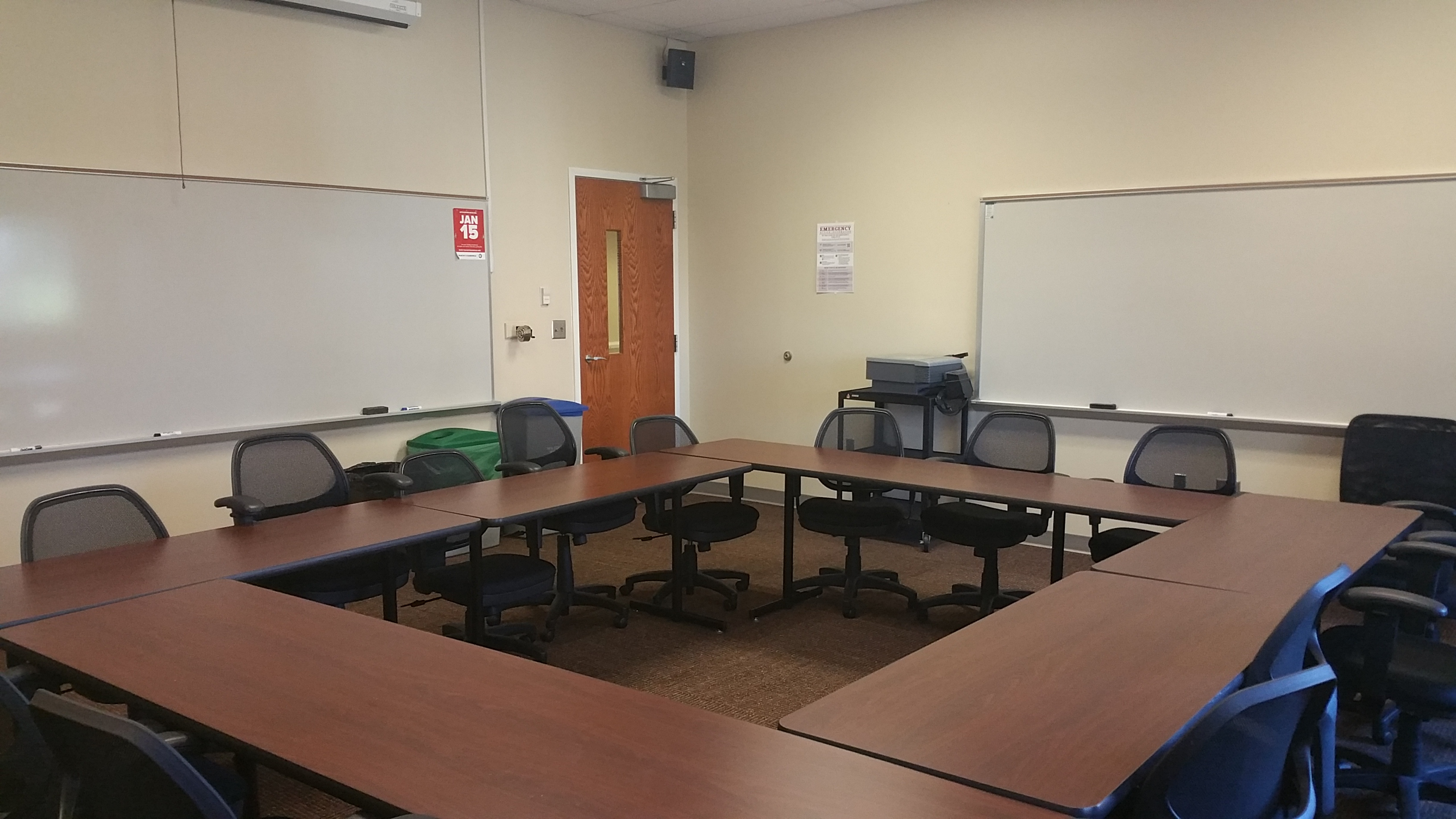 Photo of room taken from the back of the classroom showing student furniture and white boards