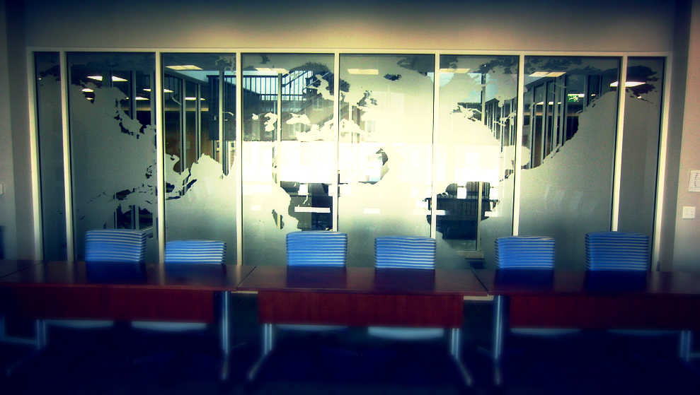 Photo of desk area in front of a glass world map