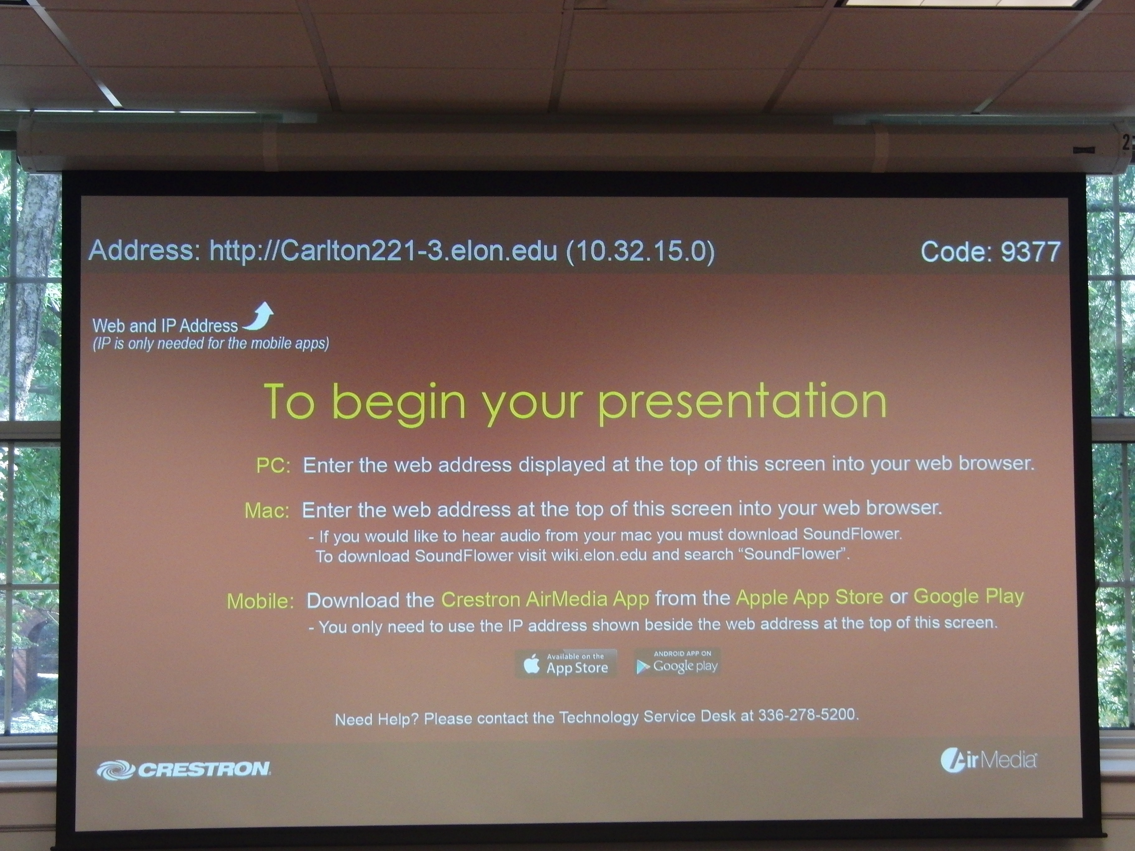 Photo of projection screen showing AirMedia information including web address and code