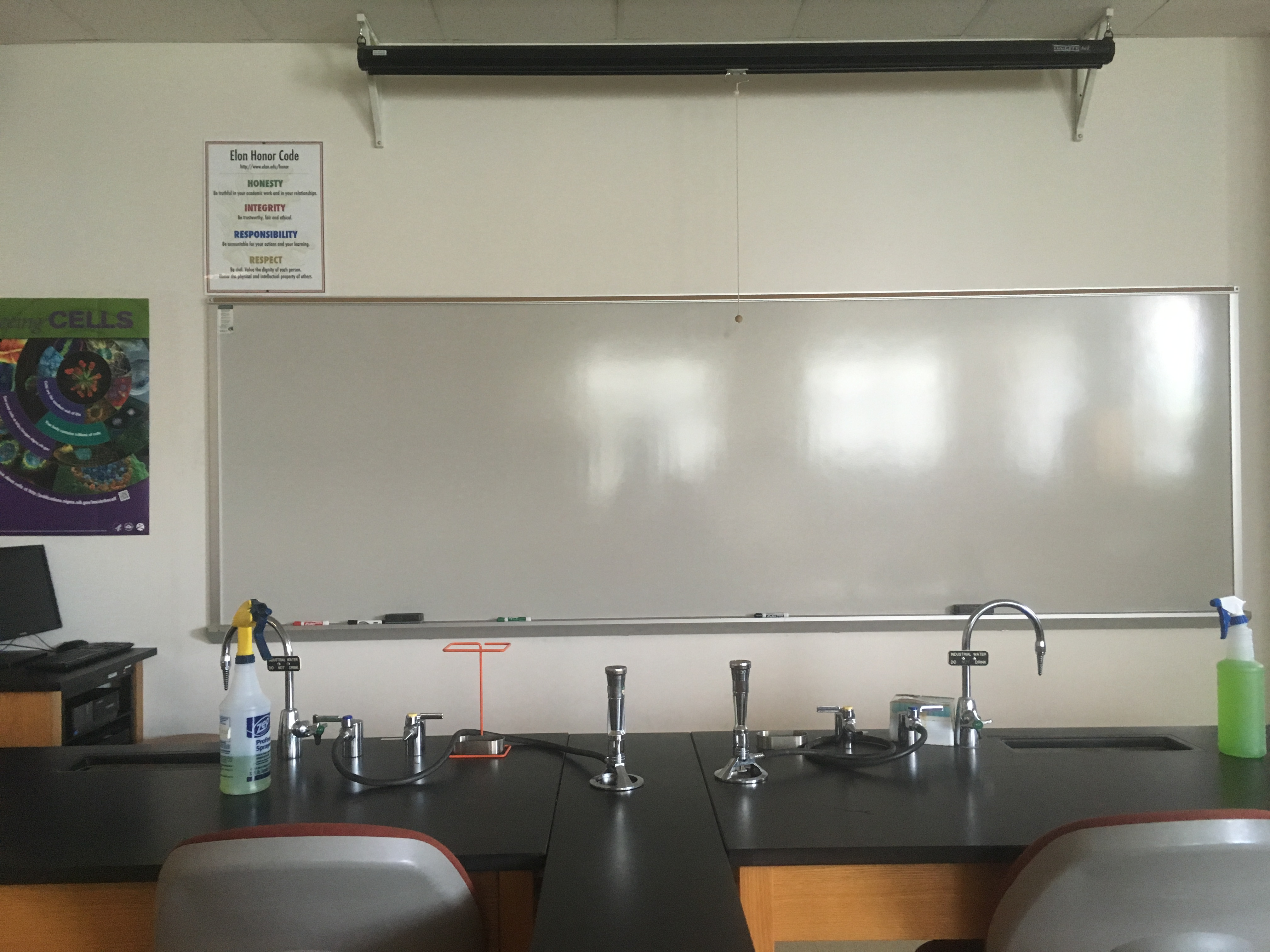Photo of the instructor area including the white board , computer station, and projector screen
