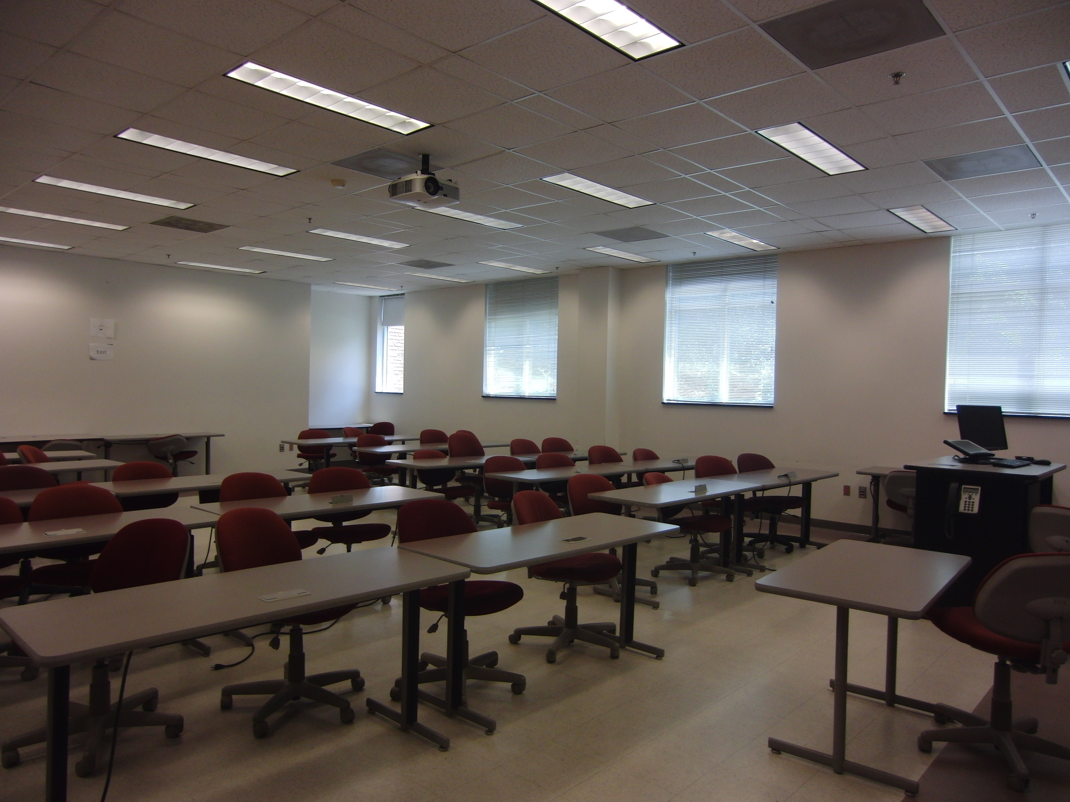 Photo of the classroom taken from the front entrance showing the stationary student tables, instructor table, and mobile chairs