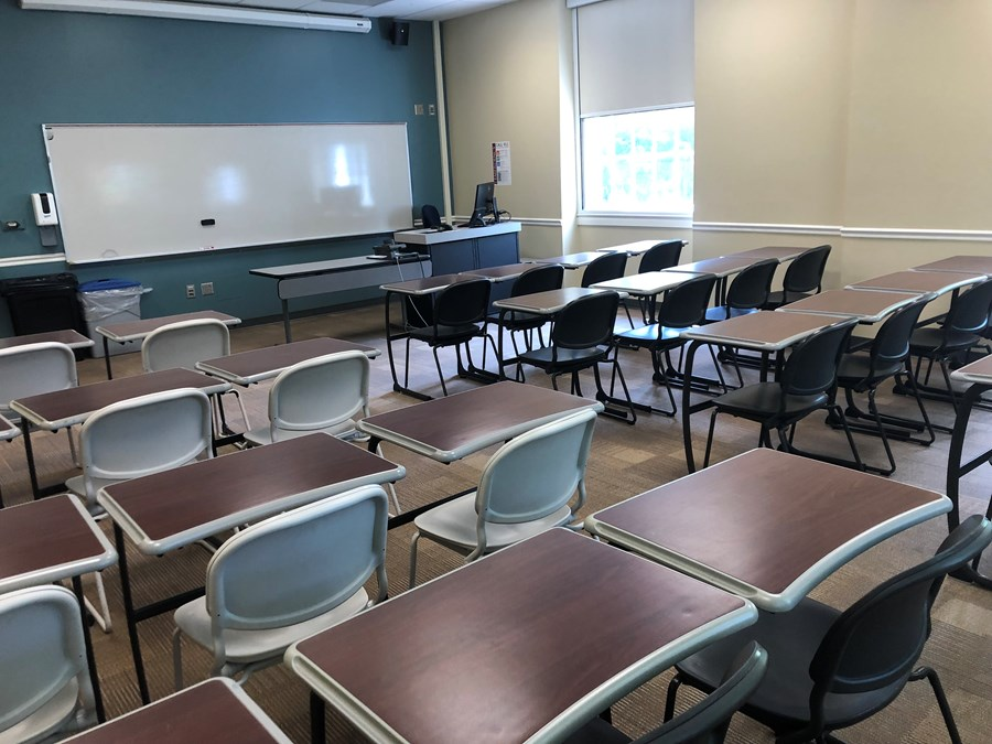 Photo of classroom taken from back left corner and includes student desks, instructor station, projection screen, and exit
