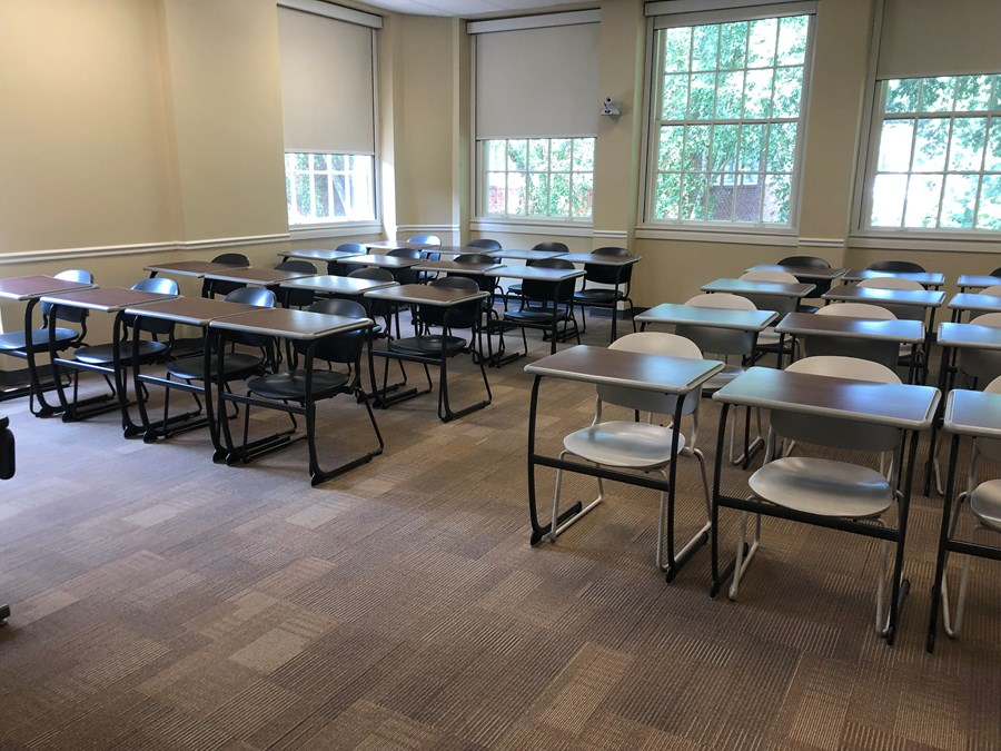 Photo of classroom taken from entrance of the room and contains student desks
