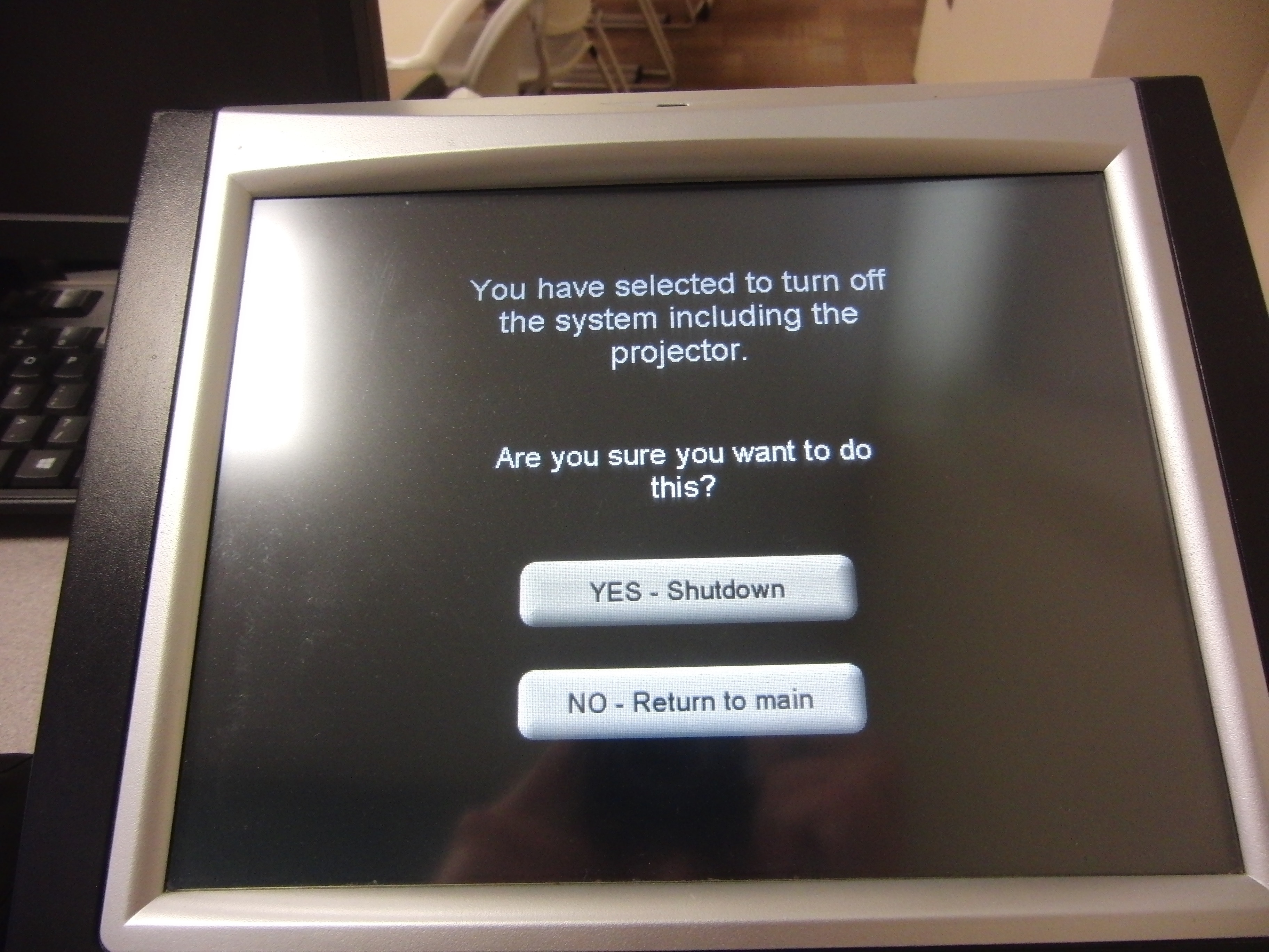 Photo of crestron control touch panel with shutdown options