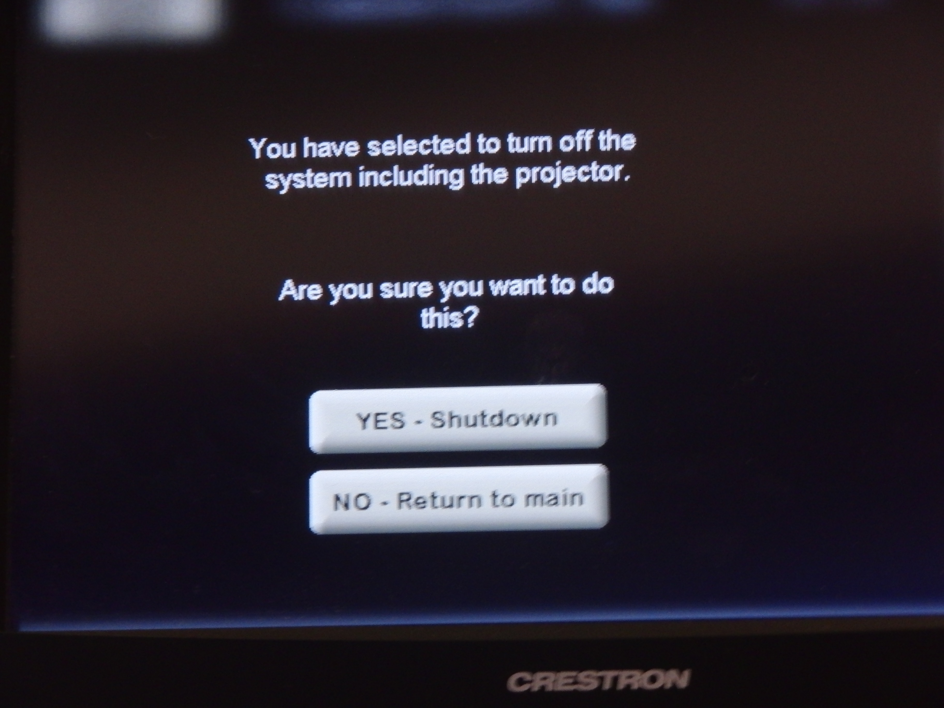 Photo of crestron control touch panel displaying the option to shut down the system