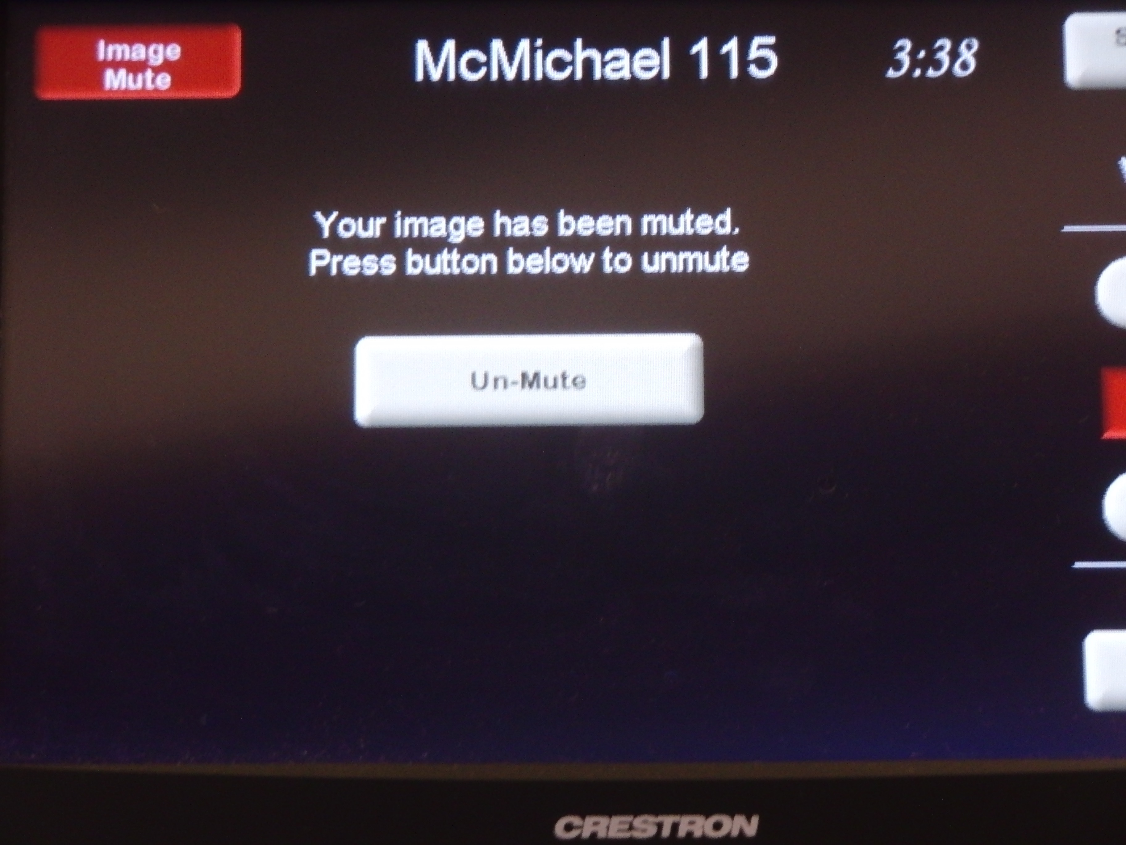 Photo of crestron control touch panel showing the option to un-mute the screen