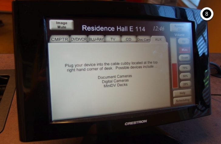 Photo of crestron control touch panel with AUX tab active