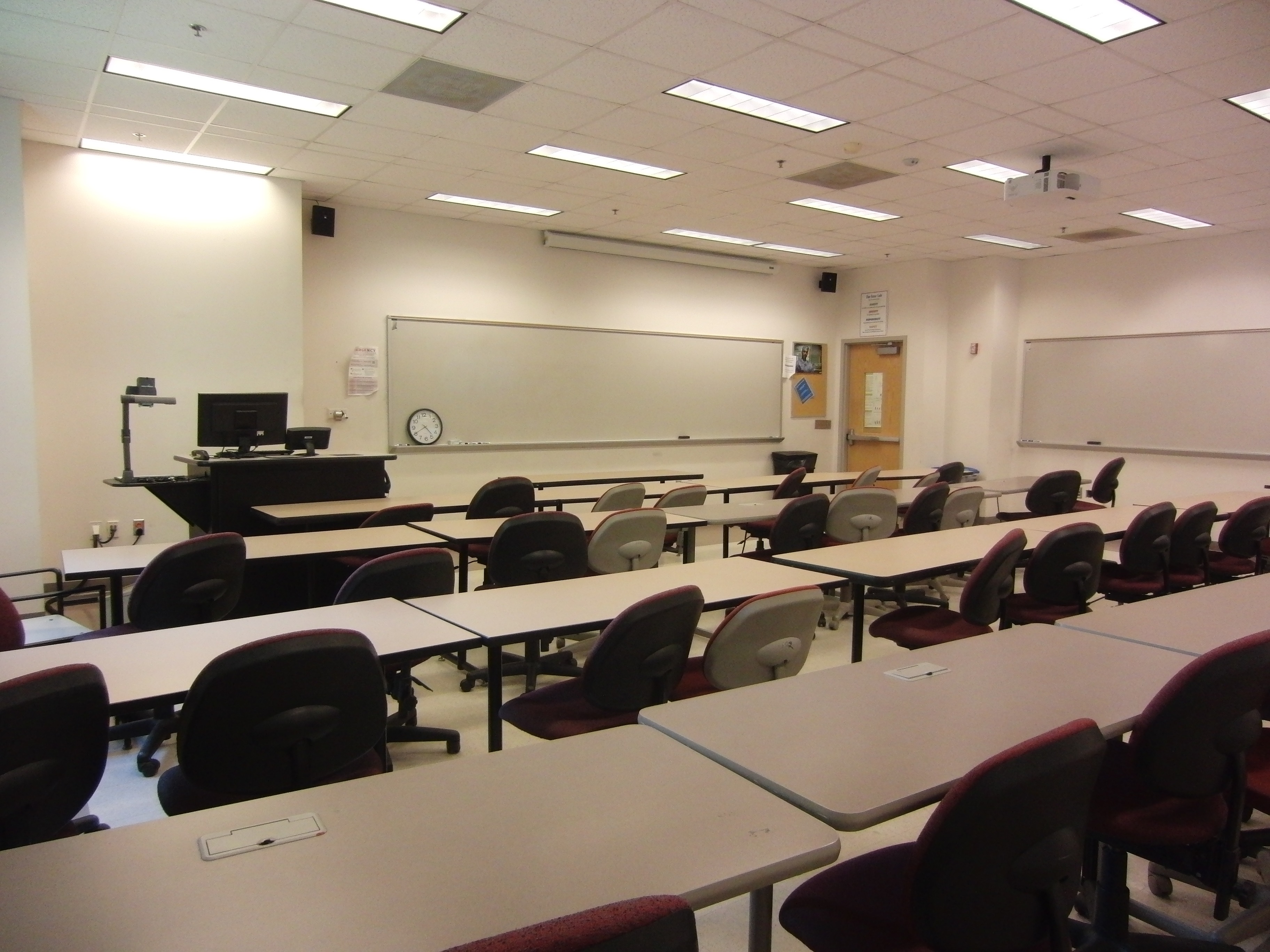 Photo of the classroom space taken from the back of the room showing stationary student desks, mobile student chairs, and the exit for the room
