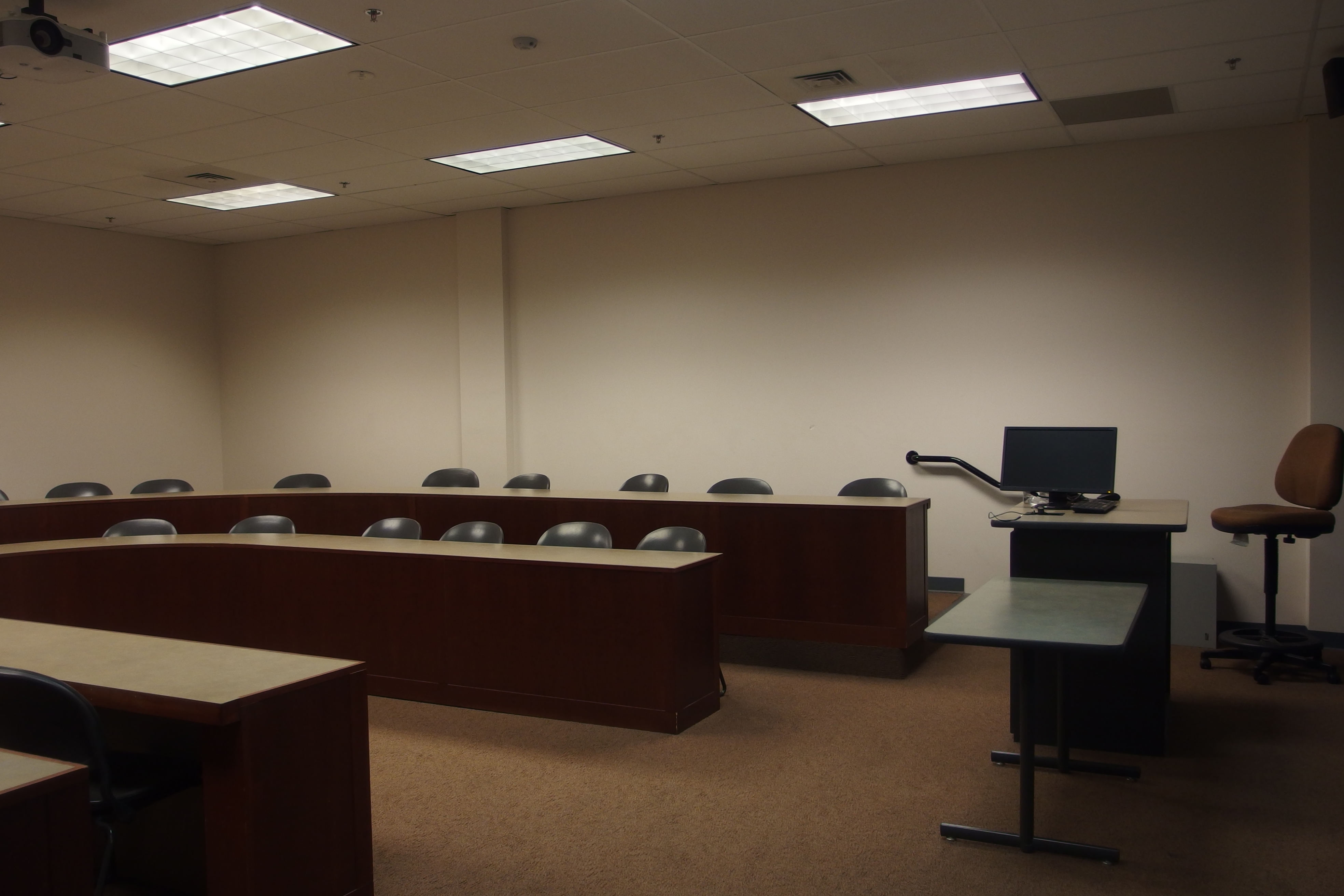 Photo fo the classroom showing the U shape table configuration and the instructor's station