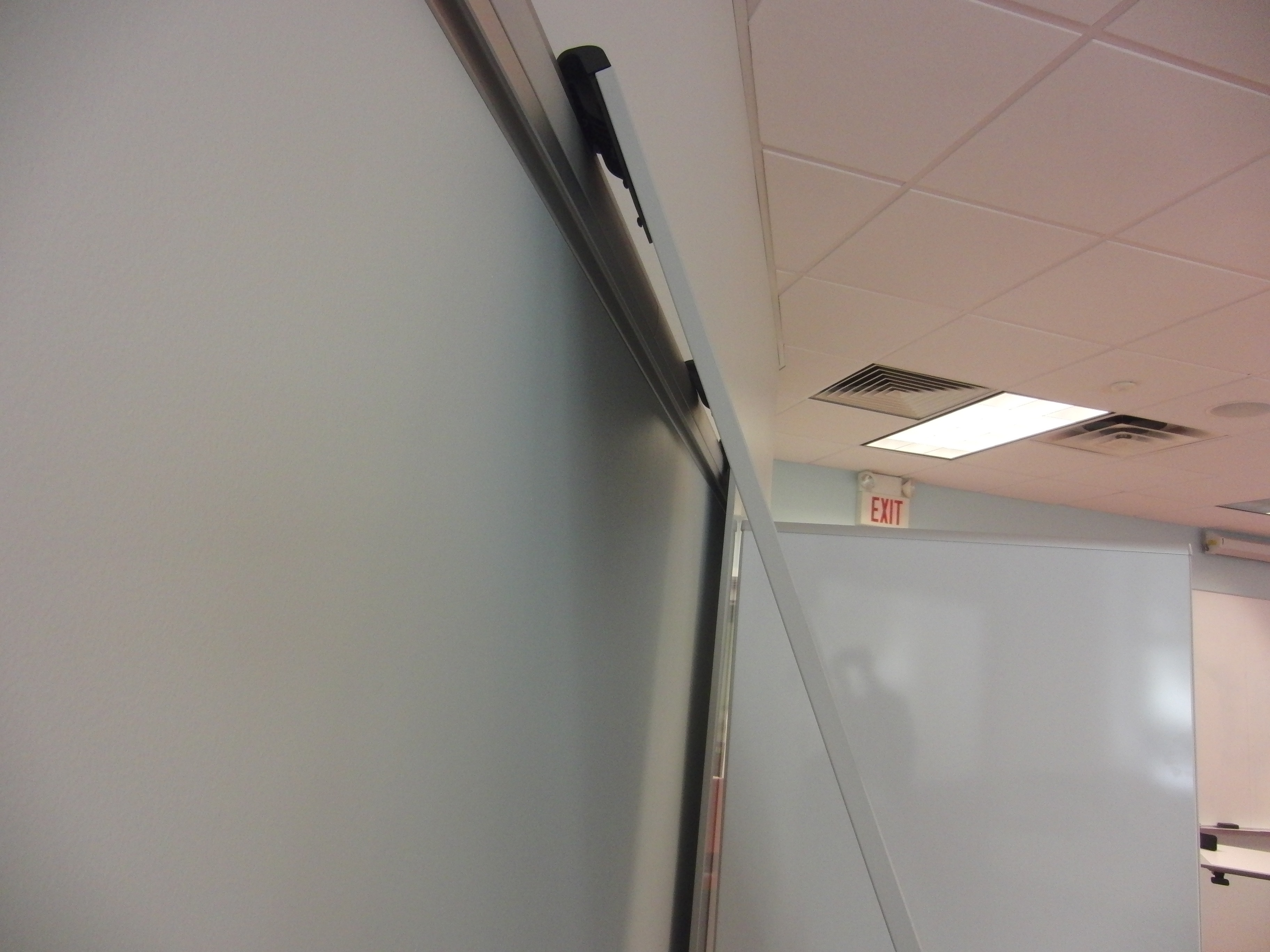 Photo of moveable white board in the process of being detached from the wall to move to another location
