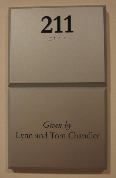 Photo of Koury Business Center 211 room number with dedication plaque placed below the room number sign.