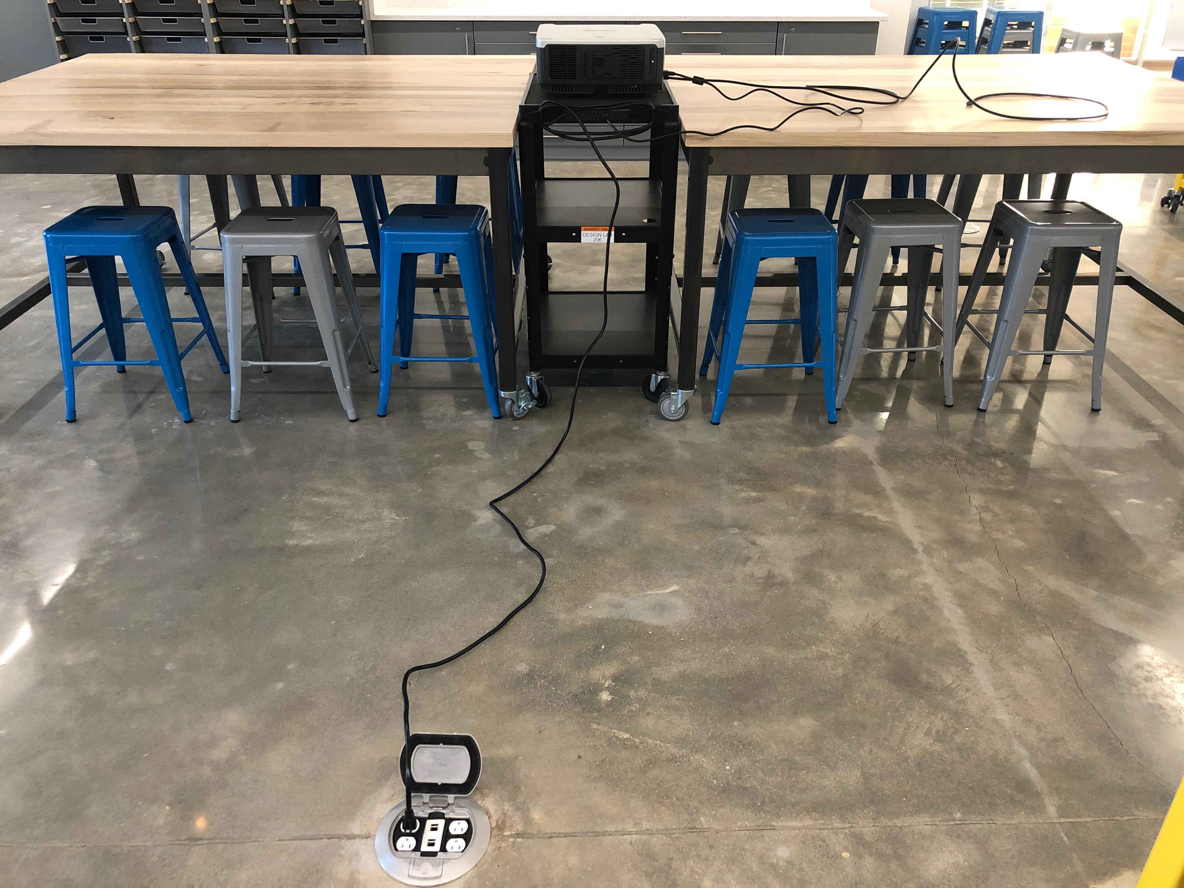 A photo from the back of the projector with the cord plugged in to the power outlet.