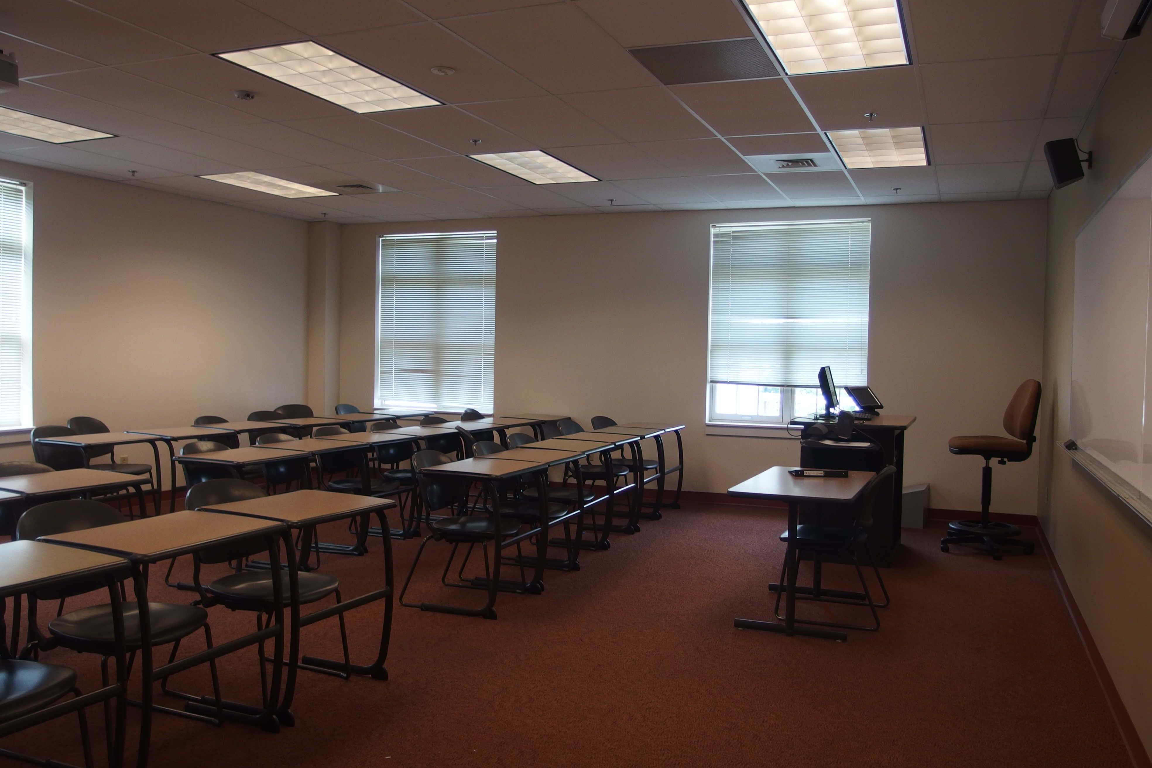 Photo of the classroom taken from the entrance of the room showing the rows of student tables as well as the instructor station