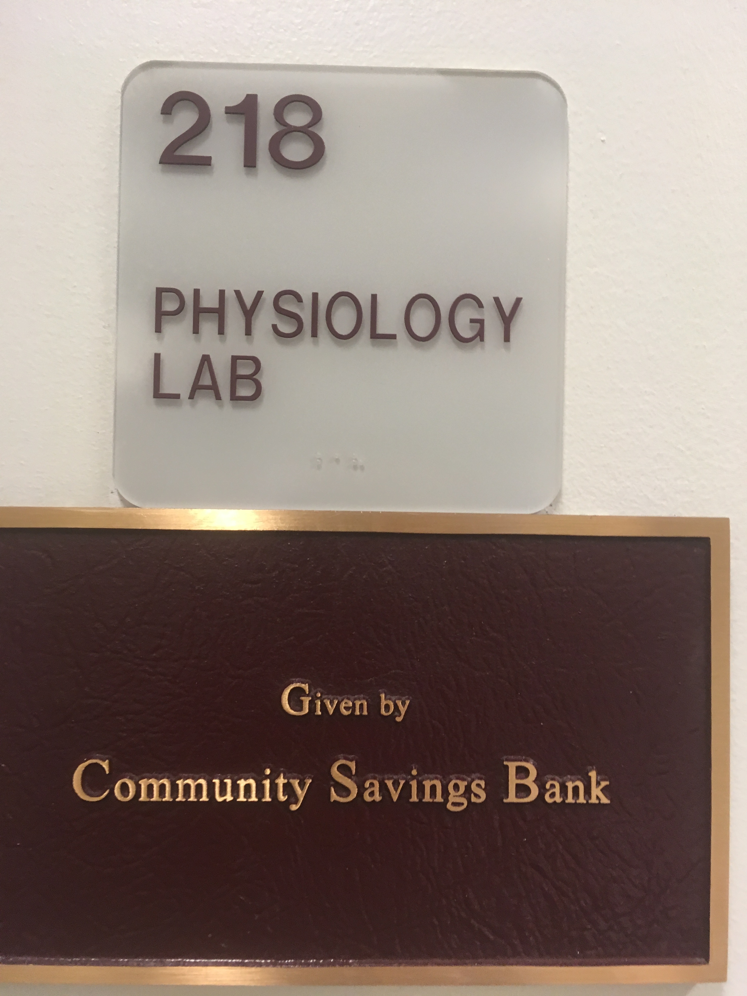 Photo of McMichael 218 room number with dedication plaque installed below