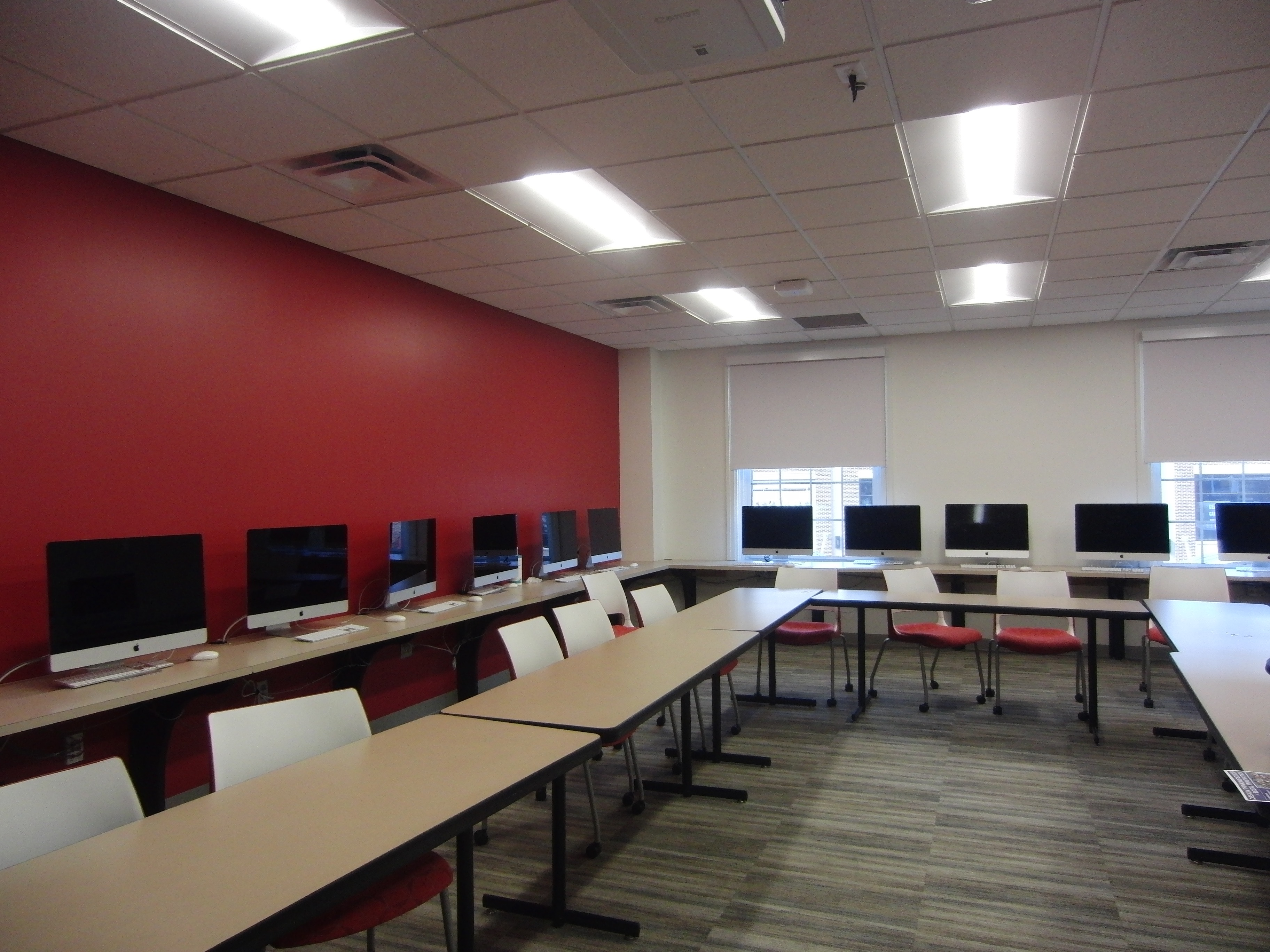 Photo of the space taken from a different angle showing computers along the wall and tables in the middle of the room