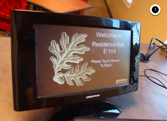 Photo of crestron control touch panel with initial screen displaying instructions to touch screen to begin
