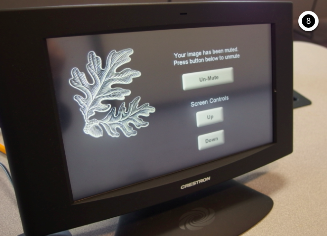 Photo of crestron control touch panel displaying the un-mute option with the ability to raise or lower the projection screen up or down