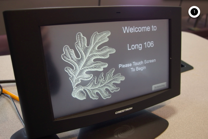 Photo of crestron control touch panel displaying the initial screen with instructions to touch the screen to begin