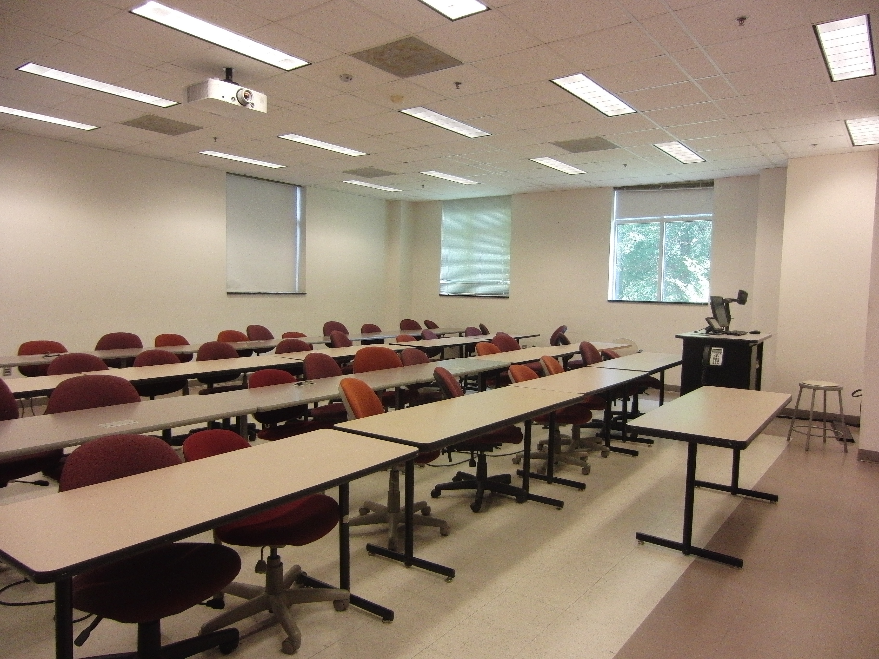 Photo of the classroom space taken from the entrance of the room showing stationary tables, mobile chairs, and the instructor's station