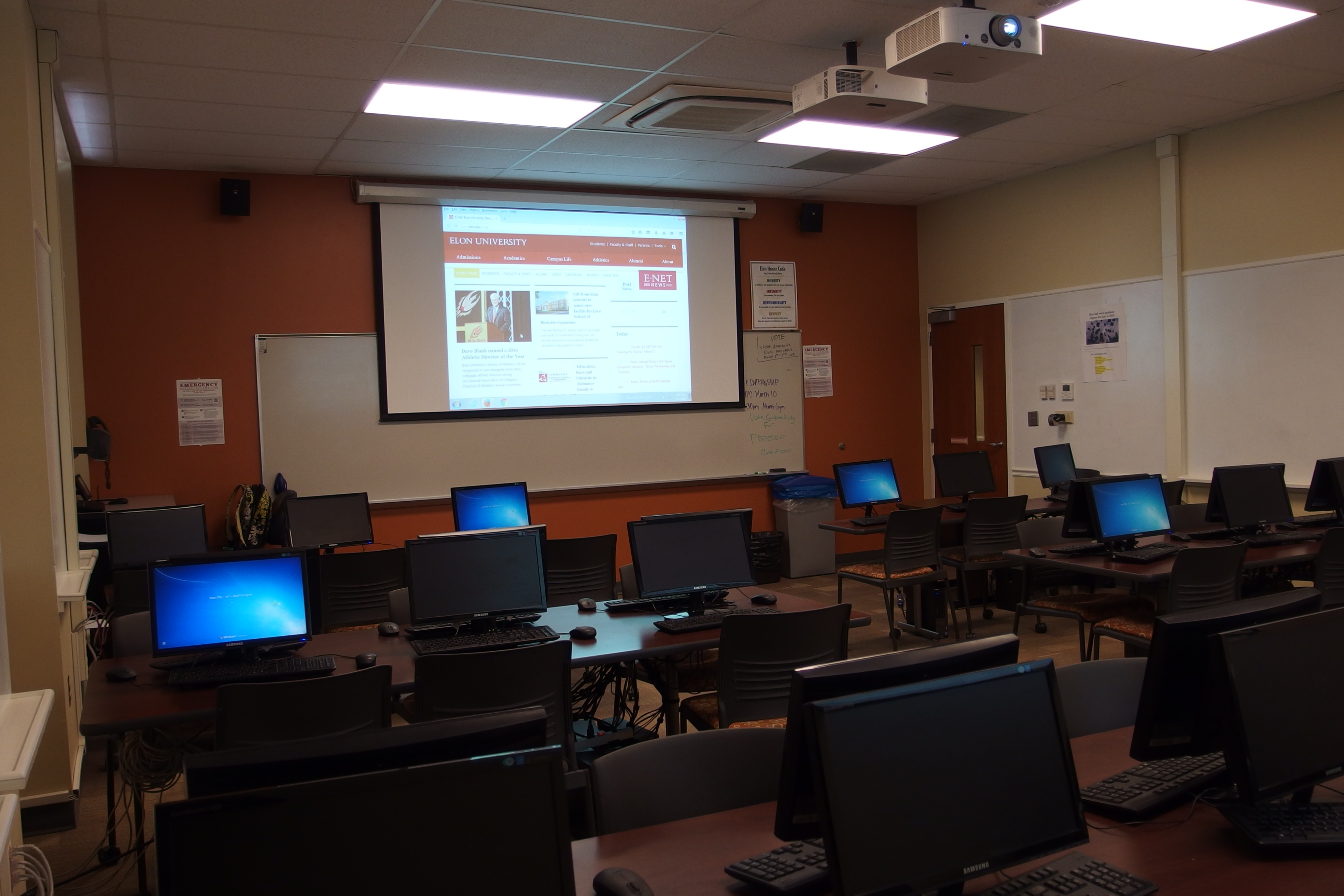Photo of classroom taken from the back right corner and includes projection screen, student work stations, exit, white boards and instructor station
