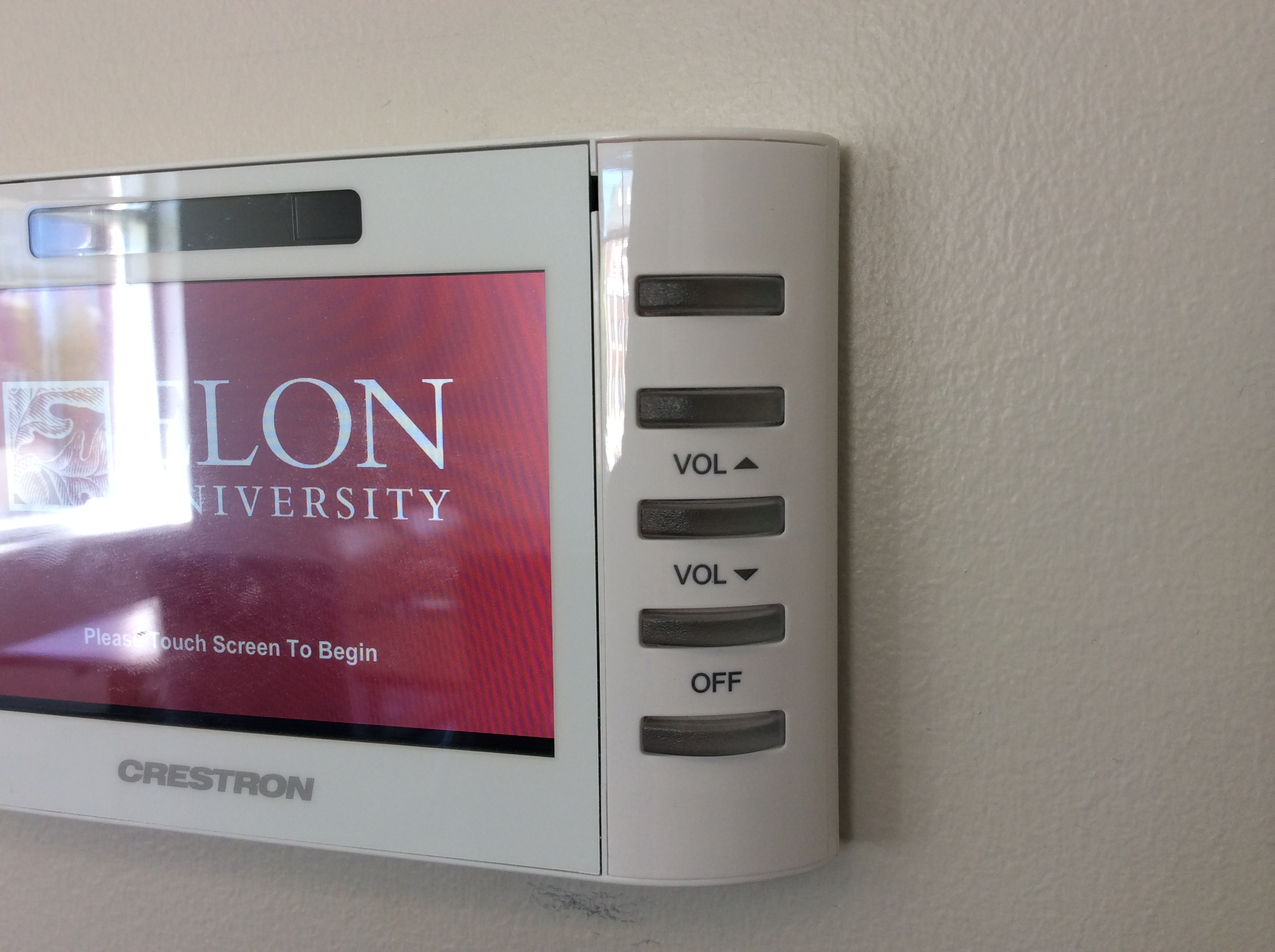 Photo of crestron control touch panel highlighting the volume up and down buttons on the right side of the wall mounted device
