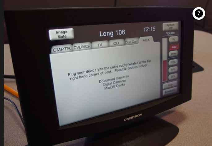 Photo of crestron control touch panel with the AUX tab active