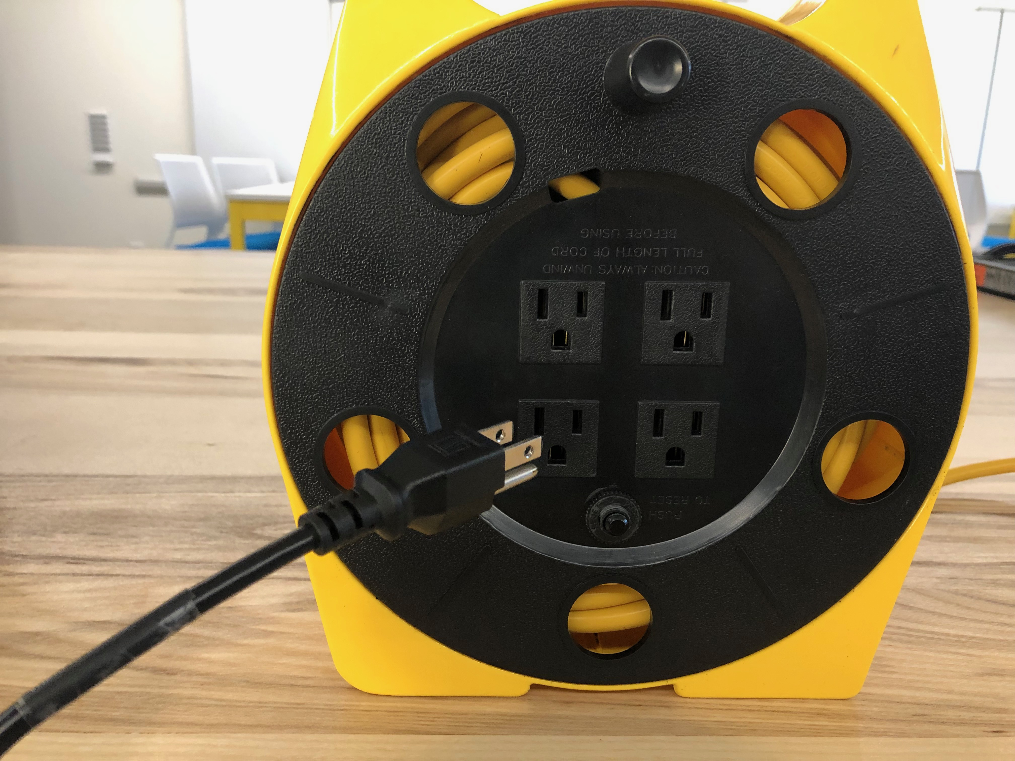 A photo of the projector plug near a power extension reel.