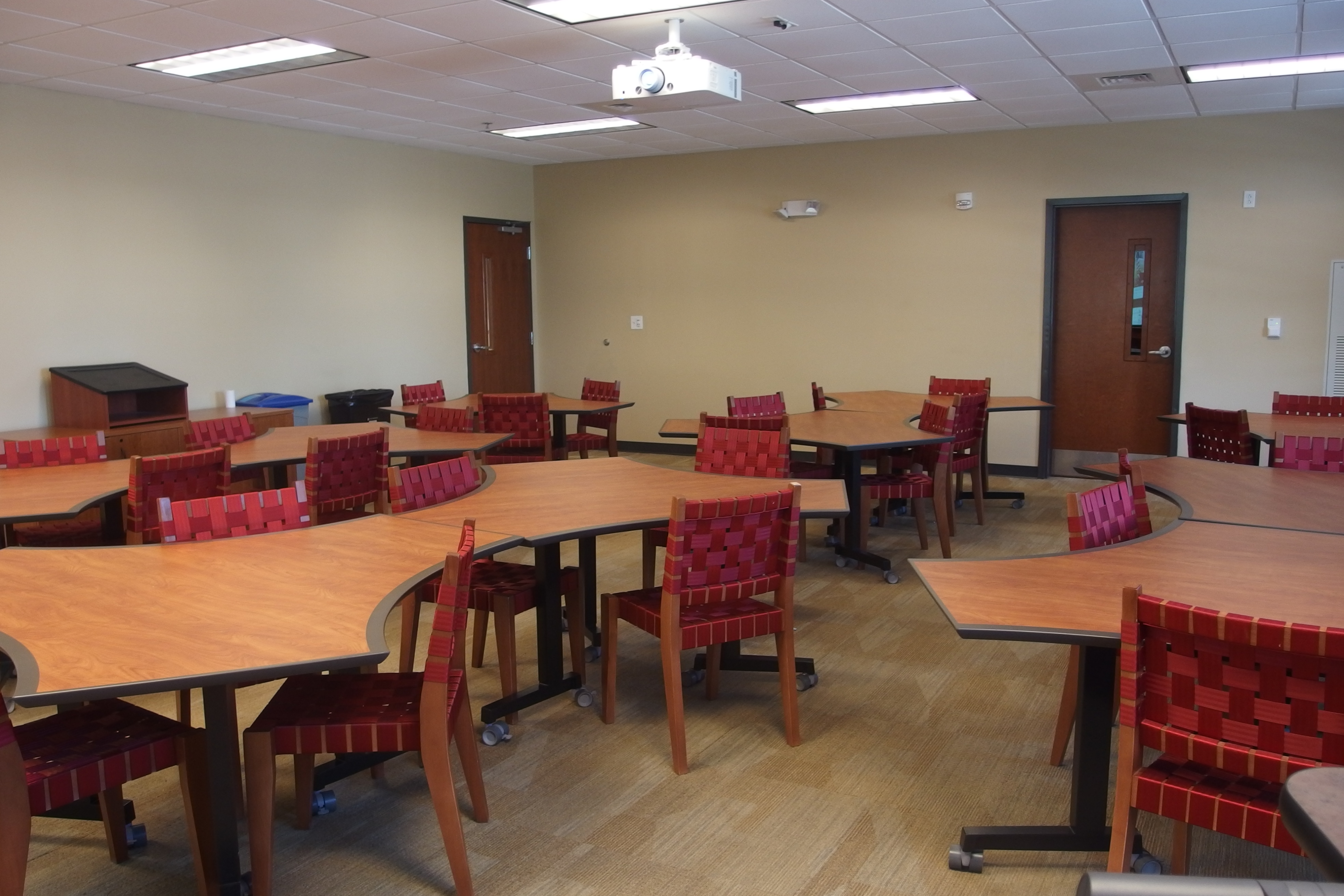 Photo of clasrrom 114 in global e taken from the front right corner of the classroom showing student working tables and chairs