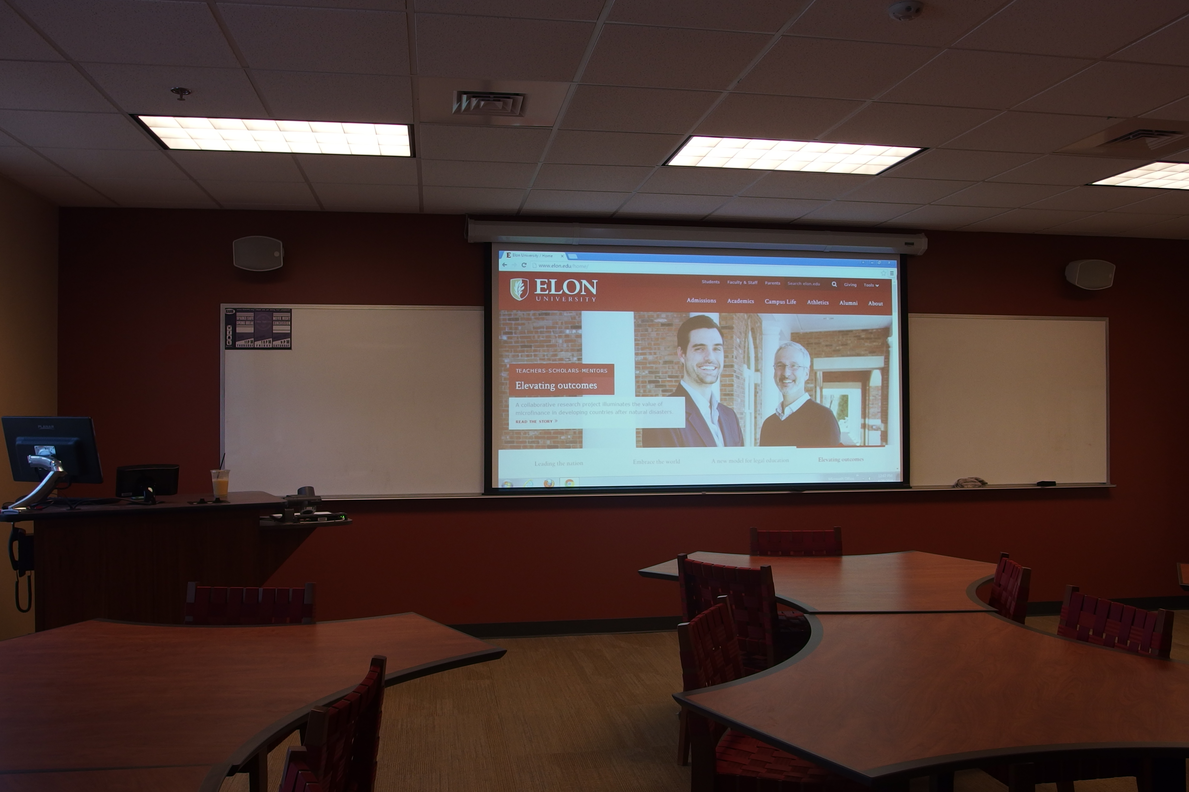 Photo of classroom 114 in global e that shows lowered projector, student tables, and instructor station