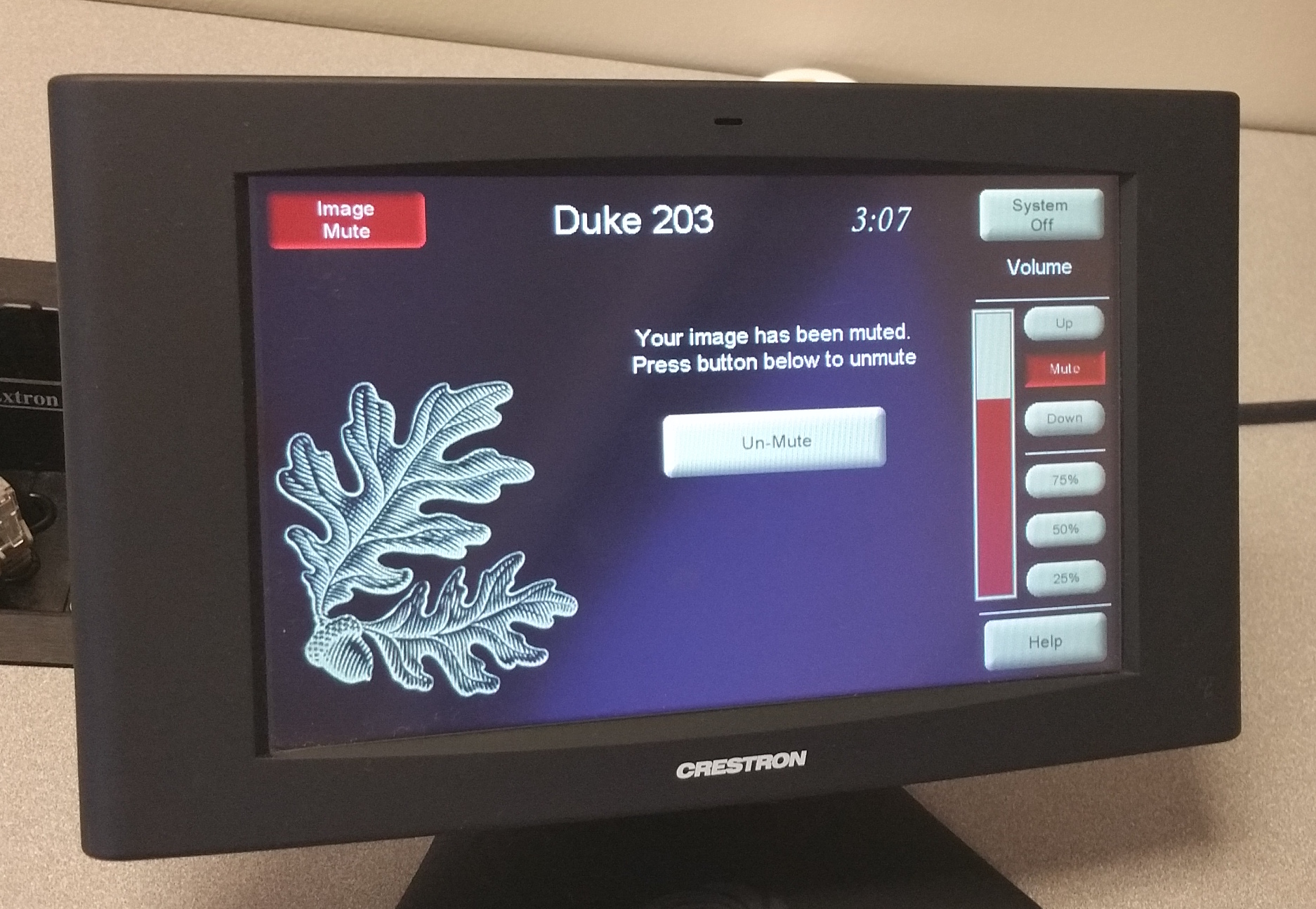Photo of crestron control touch panel with the image mute screen showing