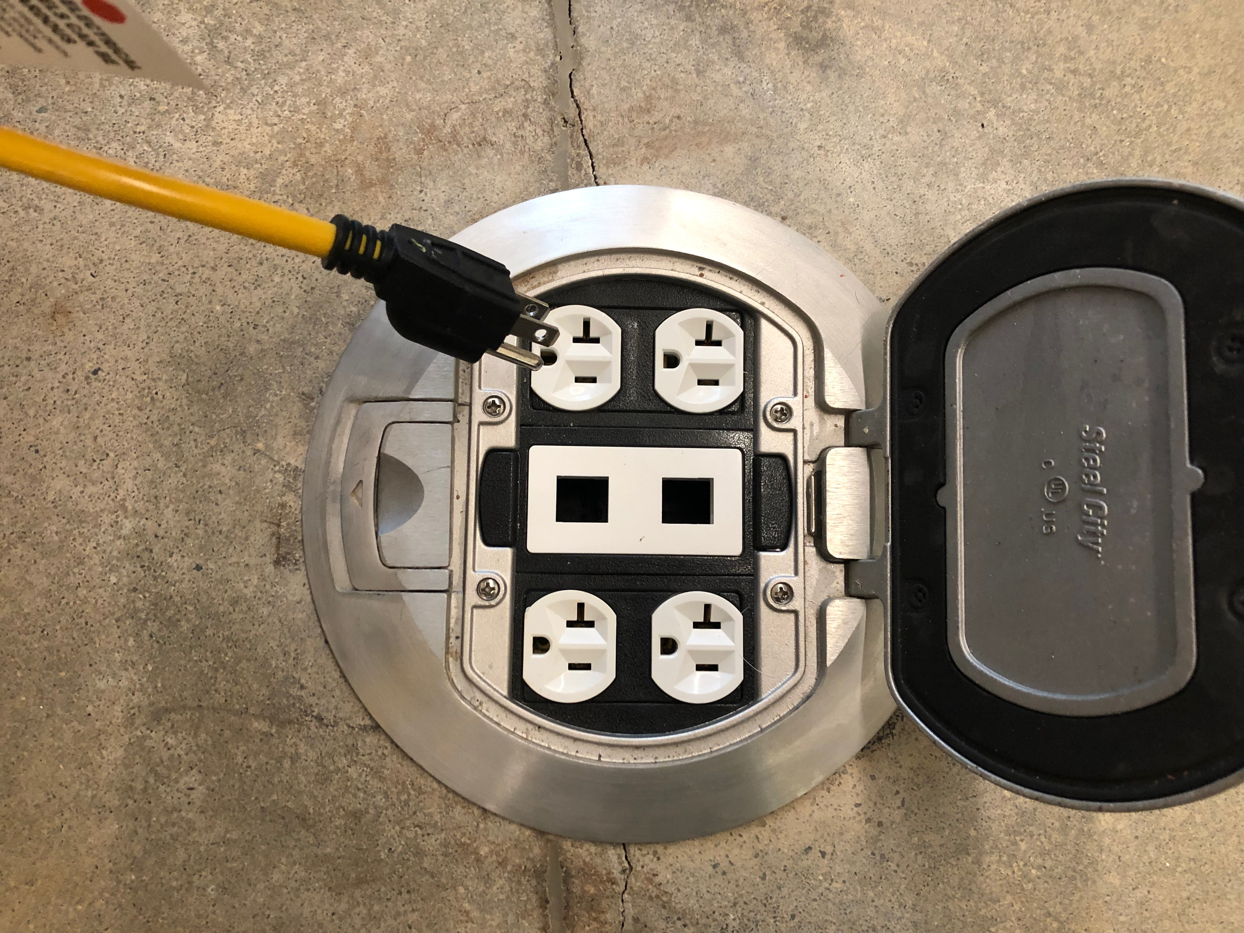 A photo of an extension cord close to the power outlet.