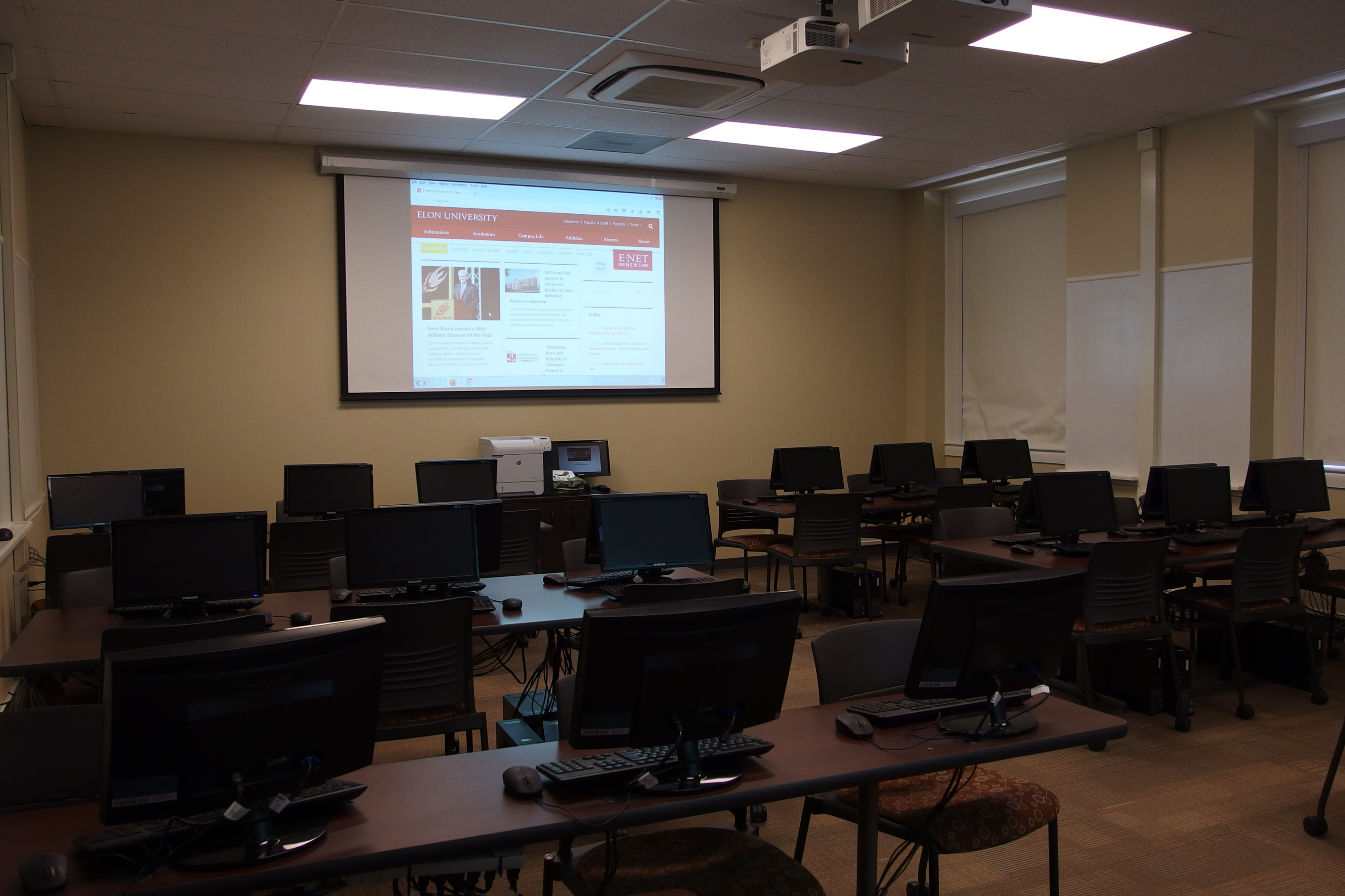 Photo of the classroom taken from the entrance of the room towards the back right corner and includes projection screen as well as student work stations
