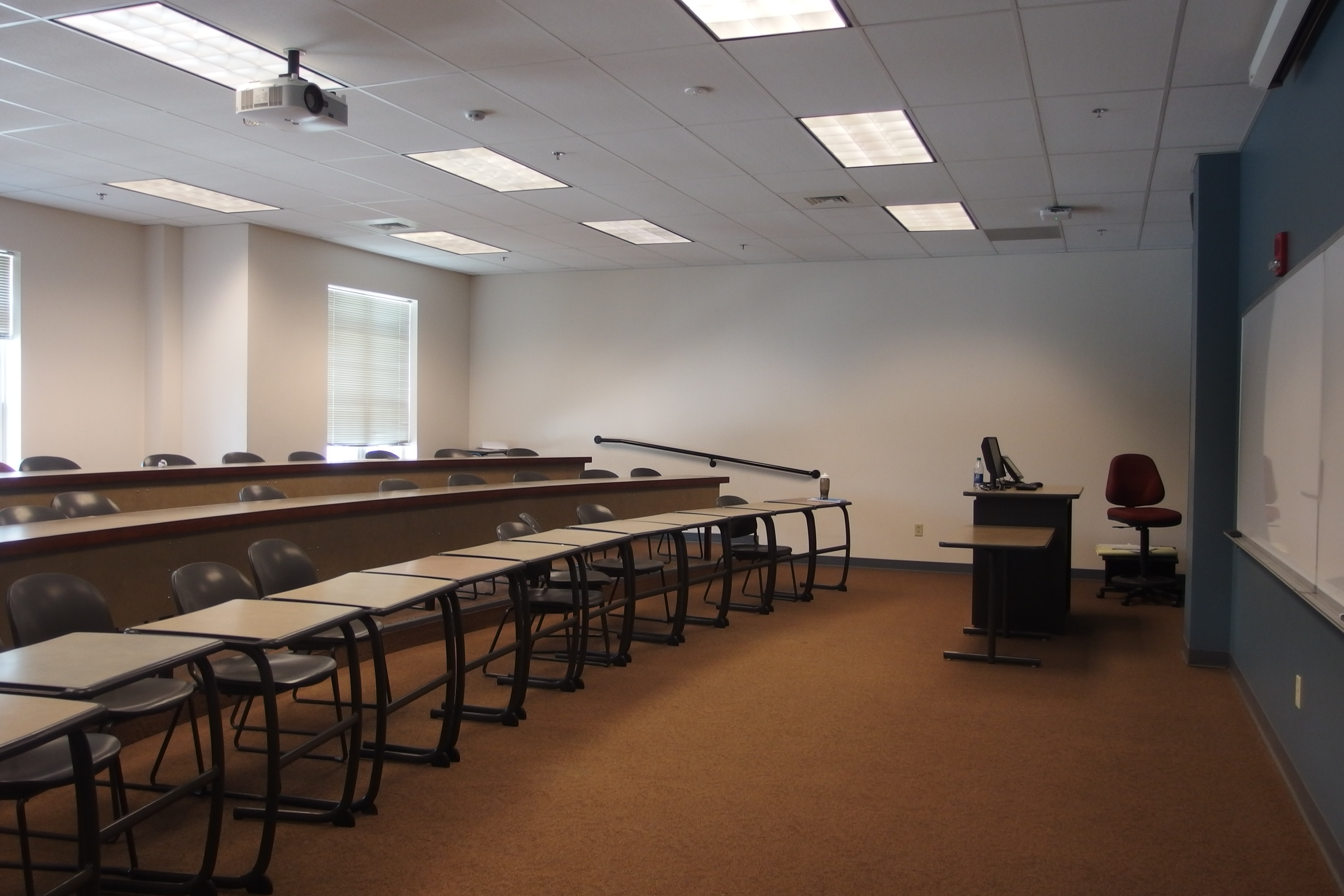 Photo of the room taken from the front center showing the instructor's station and first row of student desks