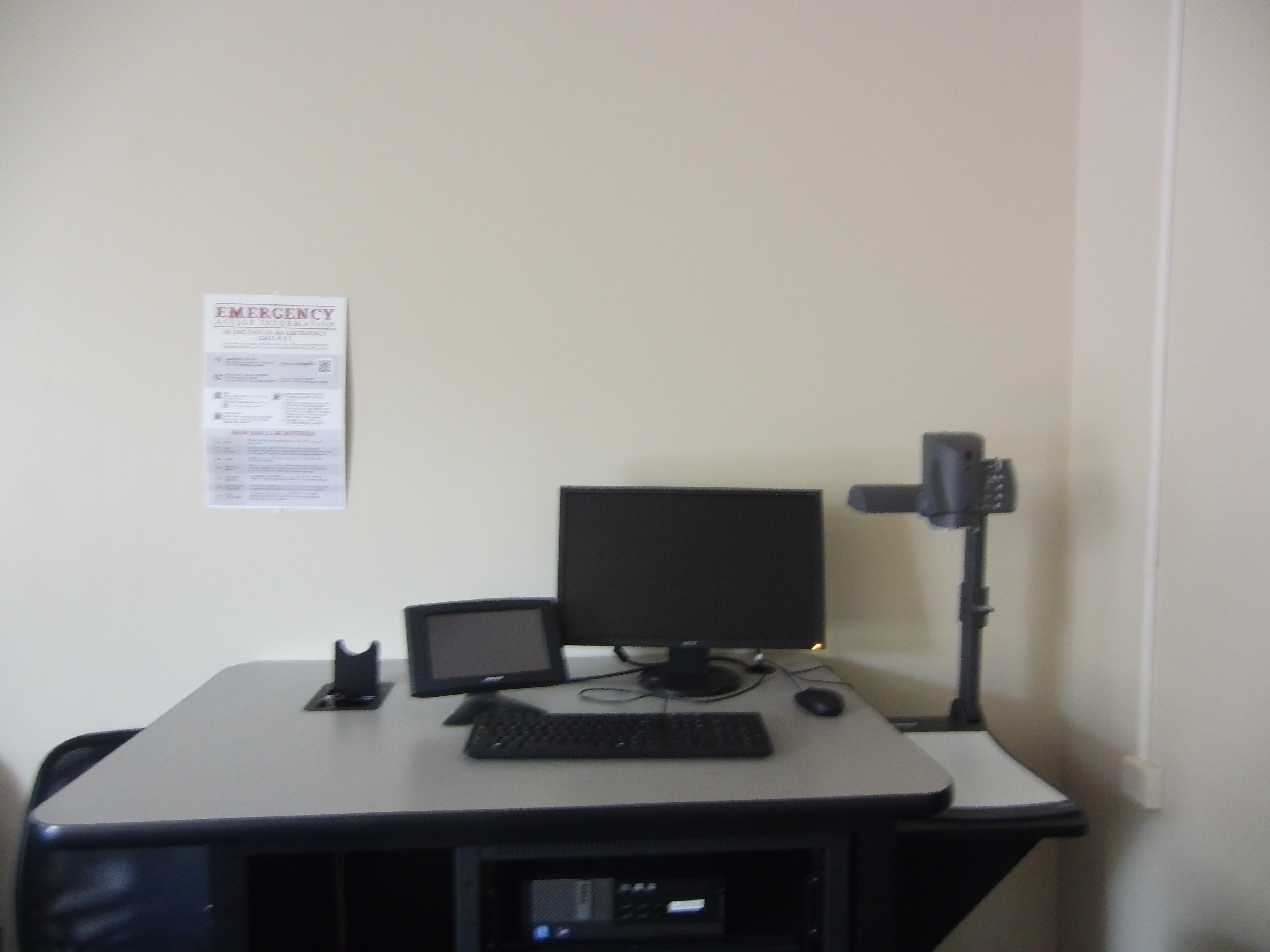 Photo of instructor station showing cable cubby, crestron control touch panel, dell computer, and document camera