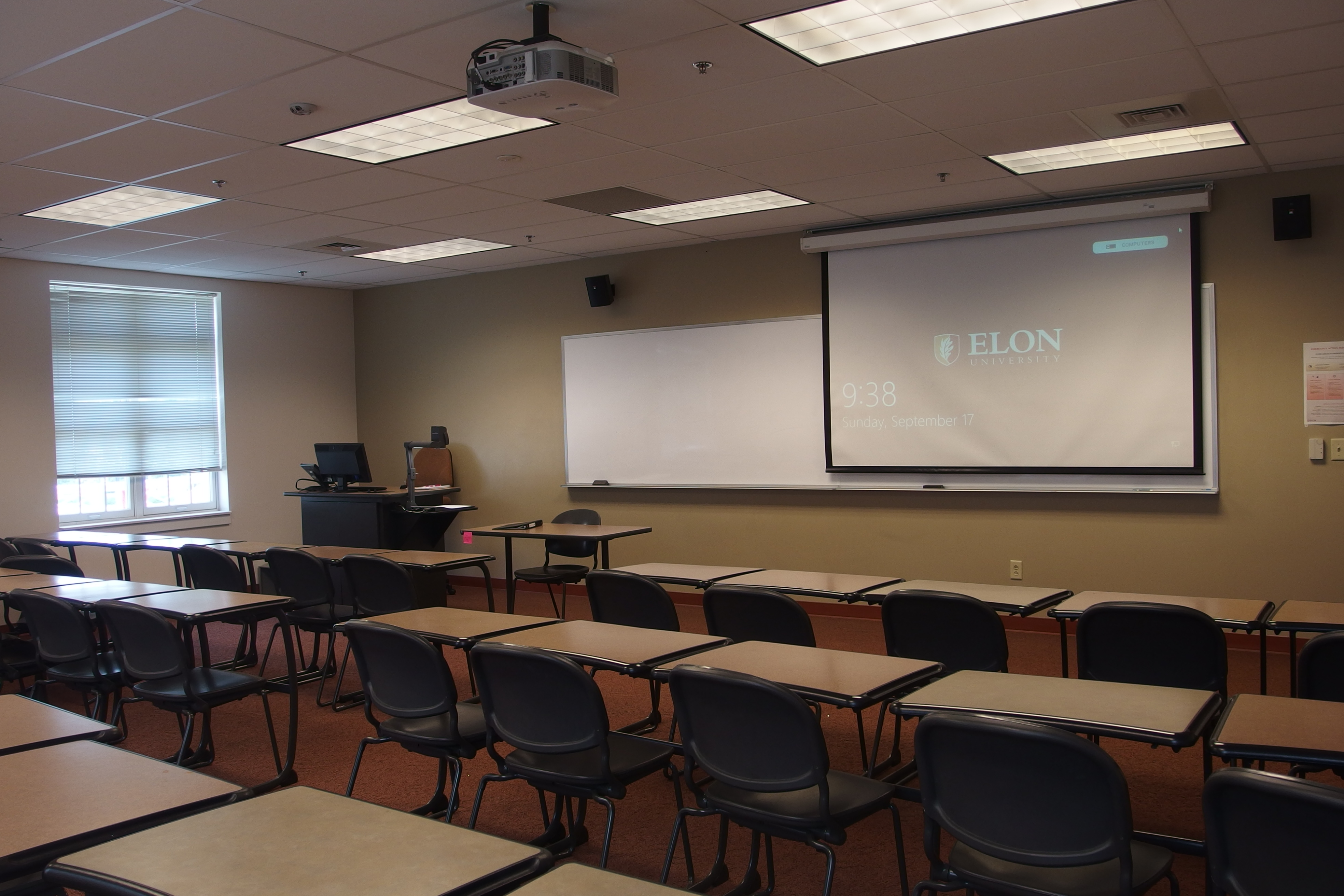 Photo of the classroom taken from the back of the class showing the student desks, lowered projection screen, and instructor's station
