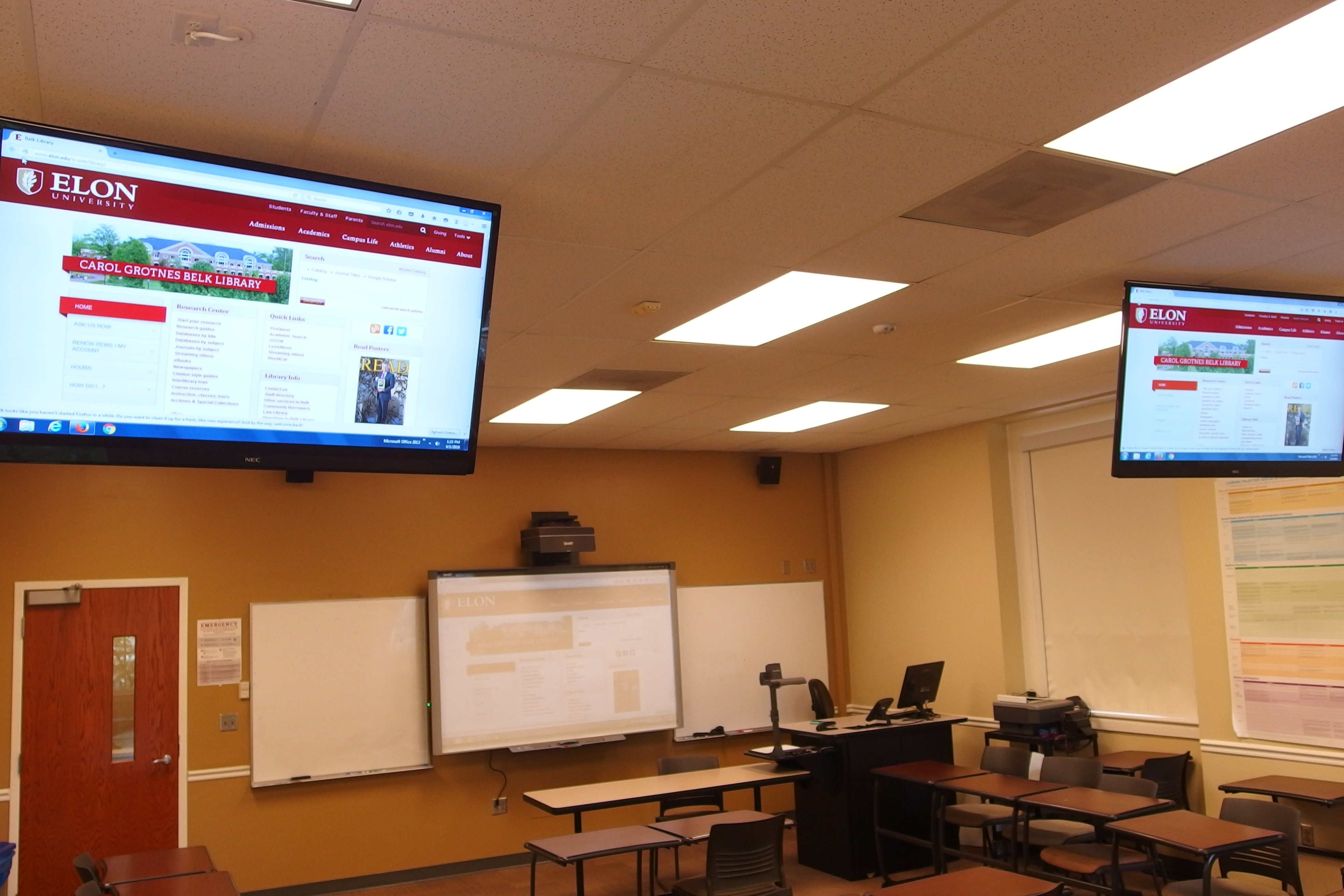 Photo of the classroom from the back left highlighting the ceiling mounted NEC tvs
