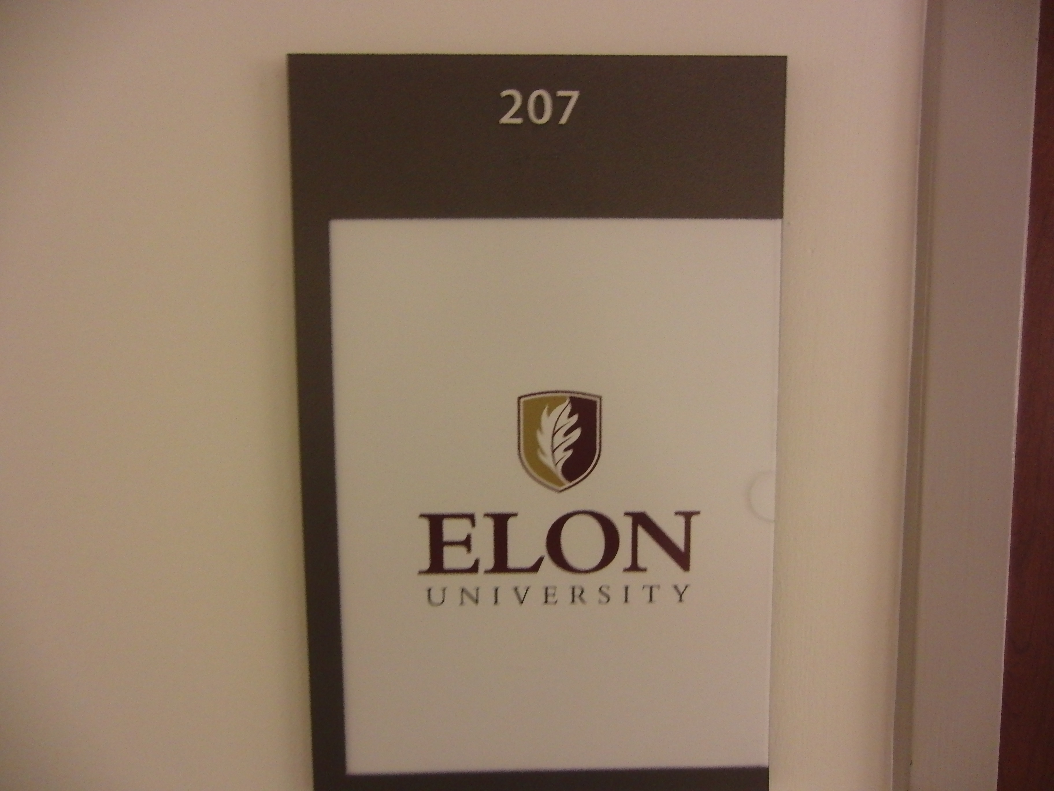 Photo of the McEwen 207 room number with room scheduling information posted below the sign