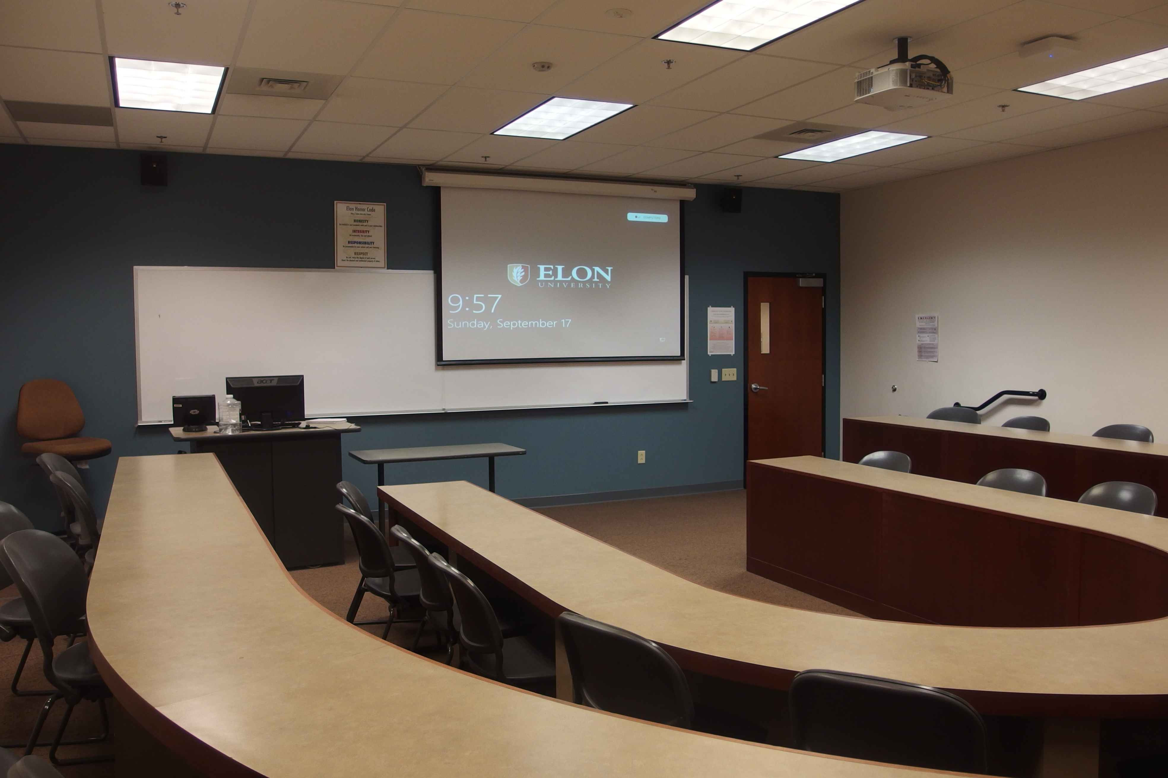 Photo of the space taken from the back of the classroom showing the lowered projector screen, the instructor's station