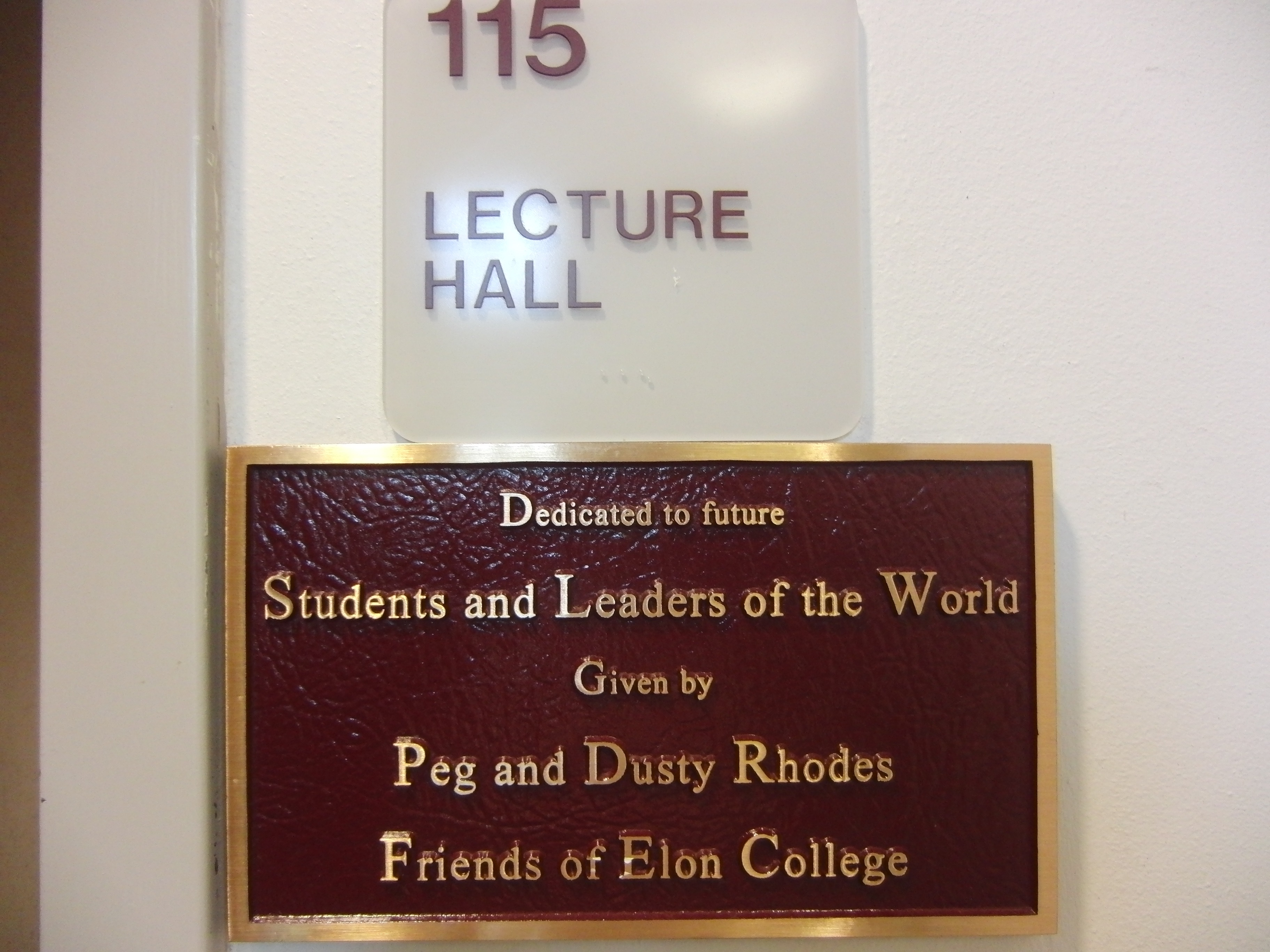 Photo of the McMichael 115 room number with dedication plaque installed below